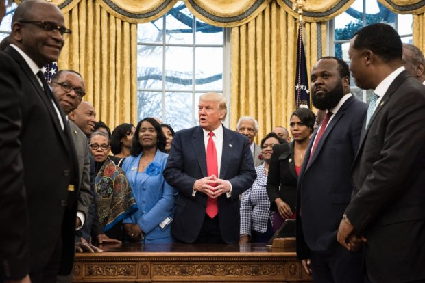 US President Donald Trump talks with leaders of historically black universities and colleges before posing for a group photo in the Oval Office of the White House before a meeting with US Vice President Mike Pence February 27, 2017 in Washington, DC. / AFP / Brendan Smialowski (Photo credit should read BRENDAN SMIALOWSKI/AFP/Getty Images)