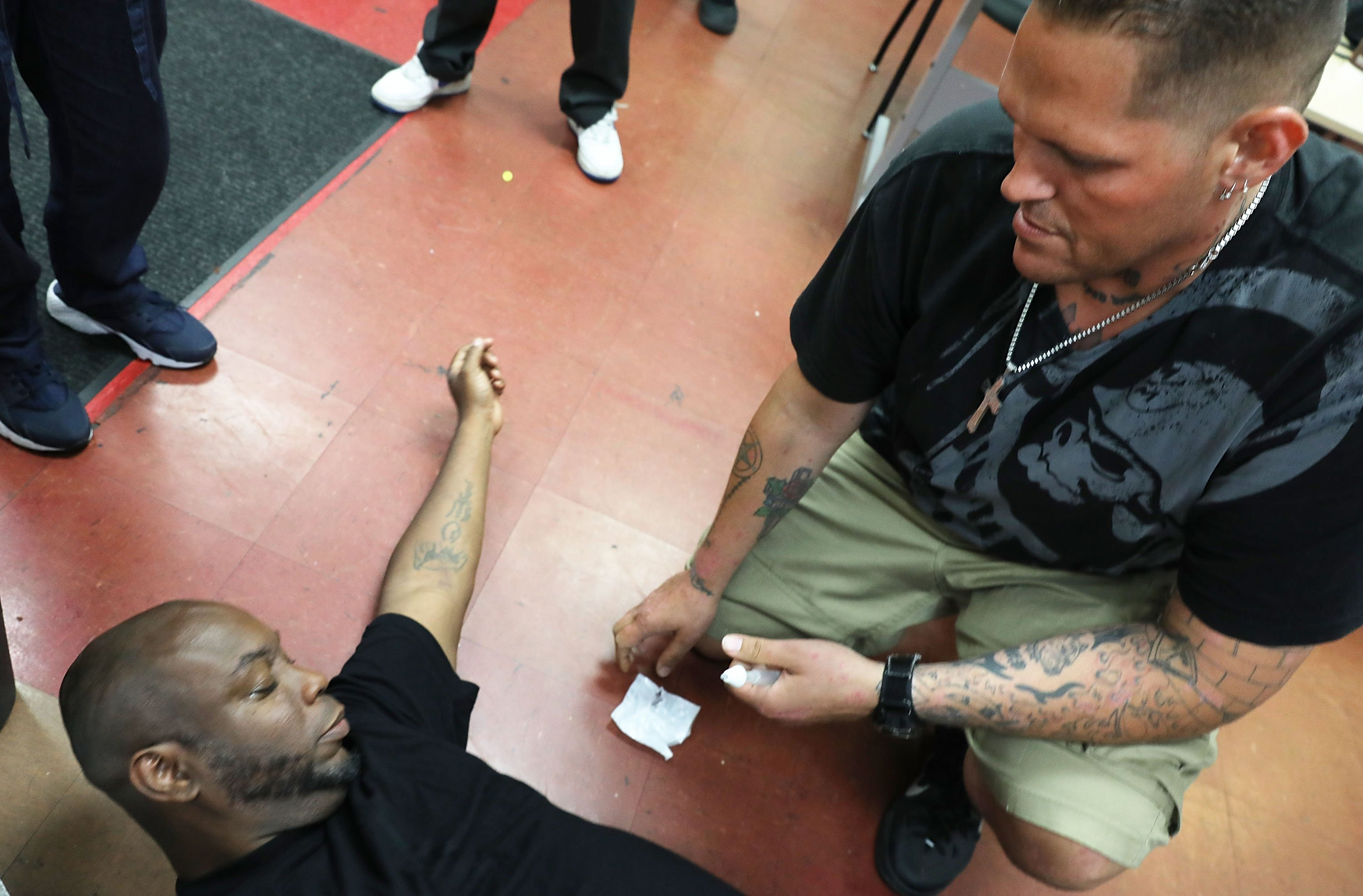 Justin, a participant in a class on opioid overdose prevention held by non-profit Positive Health Project, practices with Naloxone on teacher Kieth Allen on August 9, 2017 in New York City. (Photo by Spencer Platt/Getty Images)`
