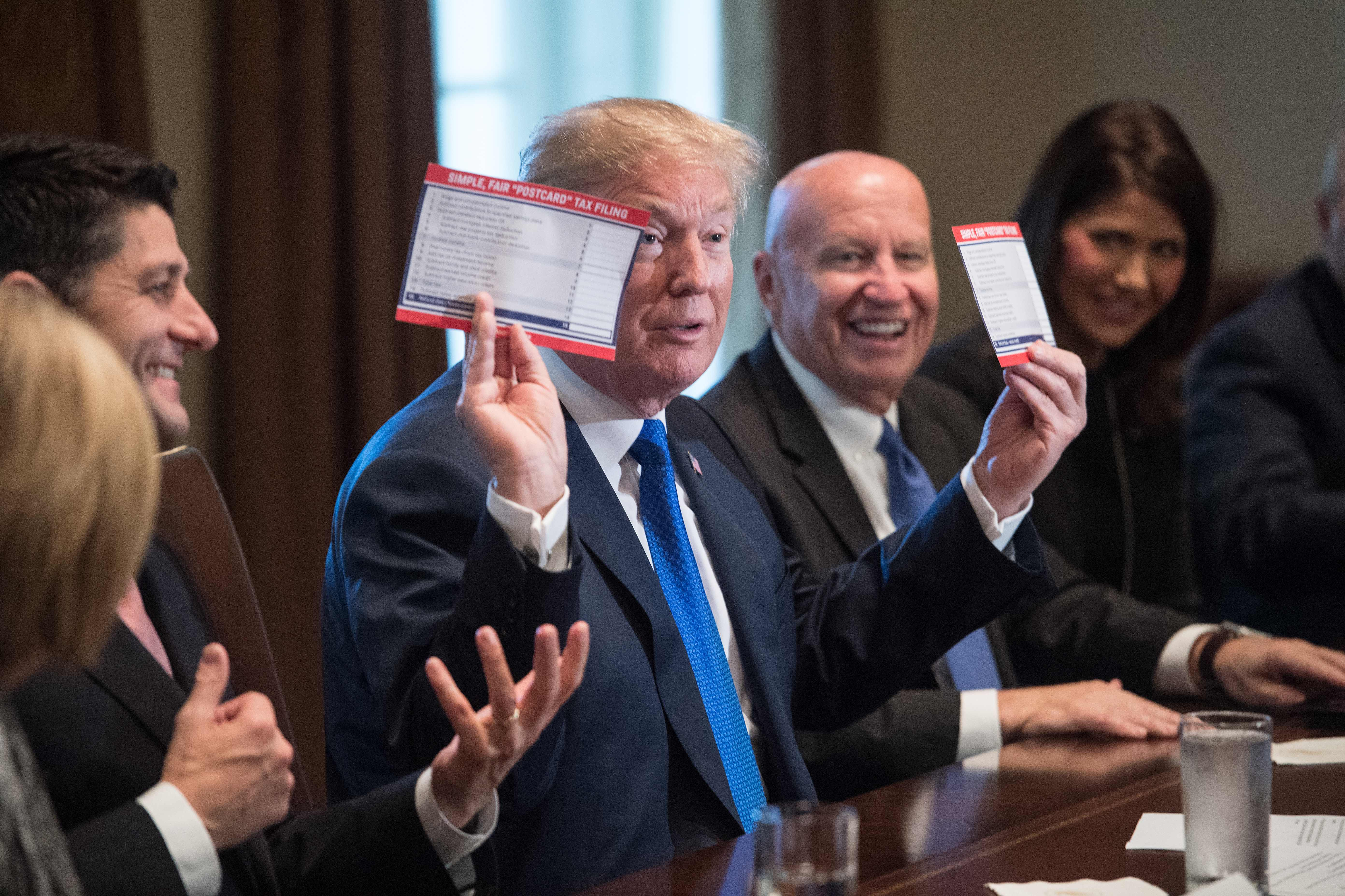 US President Donald Trump shows samples of the proposed new tax form as he meets with House Republican leaders and Republican members of the House Ways and Means Committee at the White House in Washington, DC, on November 2, 2017. / AFP PHOTO / NICHOLAS KAMM (Photo credit should read NICHOLAS KAMM/AFP/Getty Images)