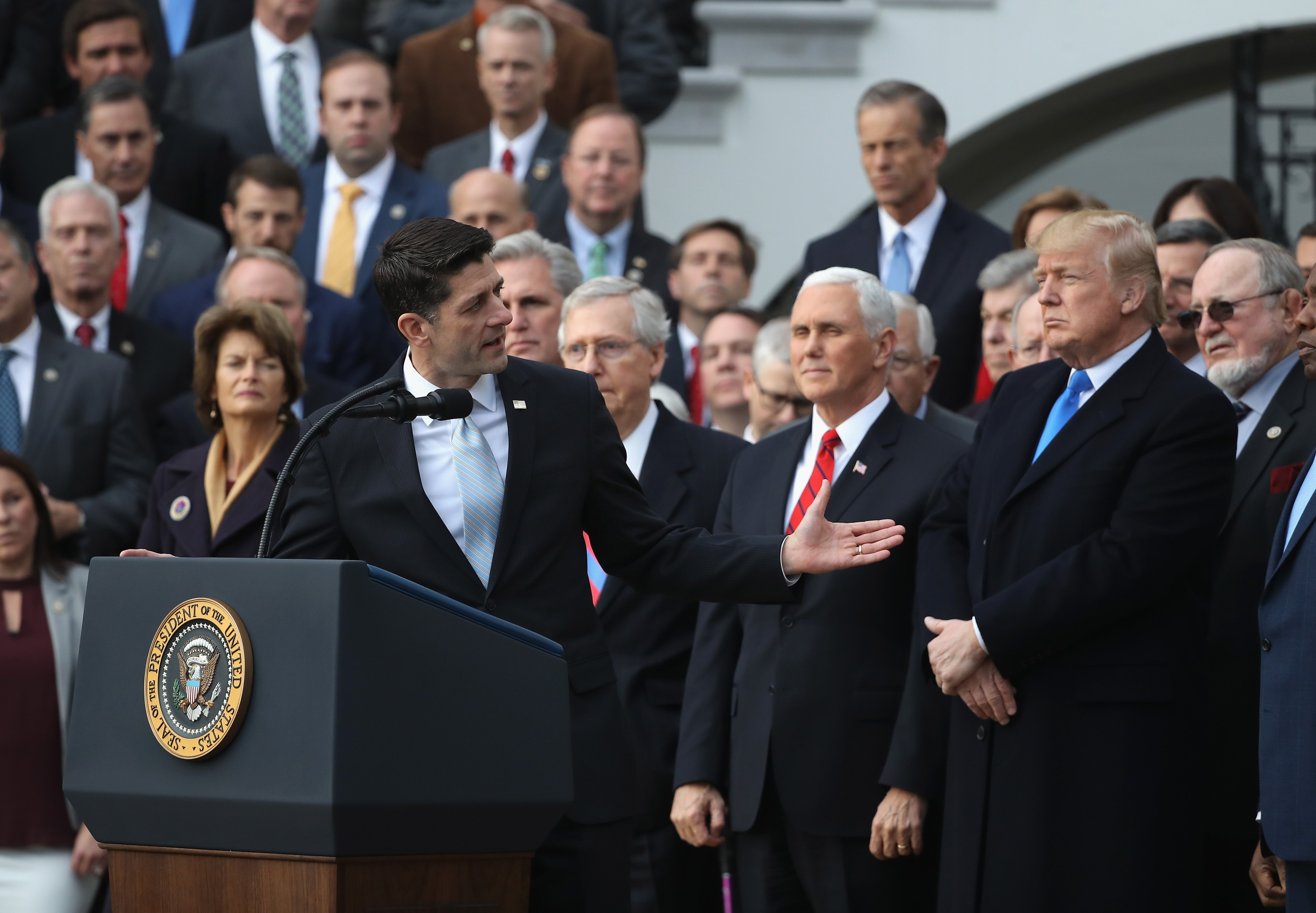 U.S. House Speaker Paul Ryan gestures to President Donald Trump, flanked by Republican lawmakers, at a celebration of Congress passing the Tax Cuts and Jobs Act on the South Lawn of the White House on December 20, 2017 in Washington, DC. (Photo by Chip Somodevilla/Getty Images)