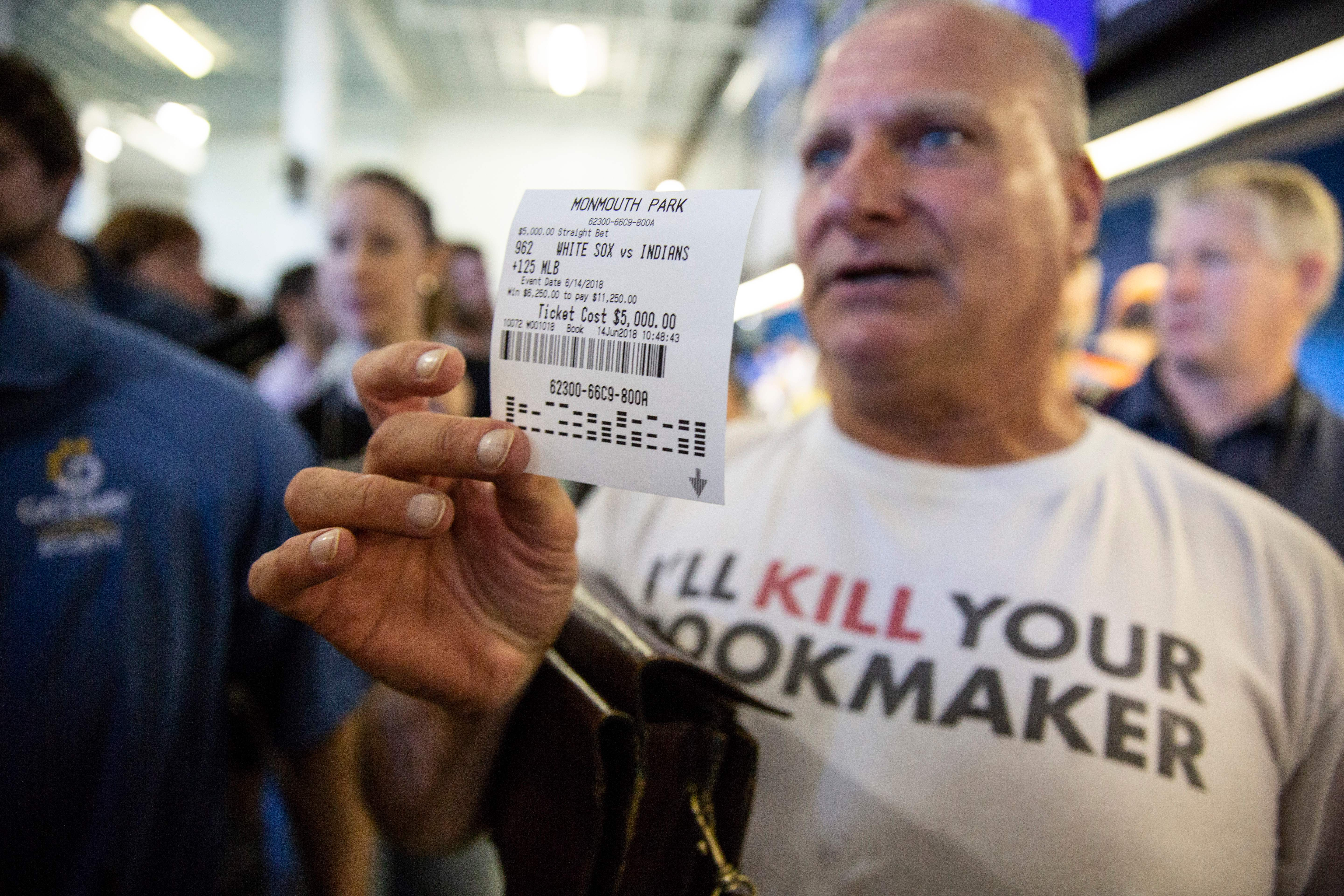 Professional odds-maker Stu Feiner holds up a betting slip for $5000 USD on June 14, 2018 after placing a bet at the Monmouth Park Sports Book on the first day of legal sports betting in the state, in Monmouth Park in Oceanport, New Jersey. - New Jersey Gov. Phil Murphy on June 11, 2018 signed a law that authorized legal sports betting in New Jersey, ending a nearly decade-long saga that included a multimillion court battle against the nation's top sports leagues and a landmark ruling from the nation's highest court. (Photo by DOMINICK REUTER / AFP) (Photo credit should read DOMINICK REUTER/AFP/Getty Images)