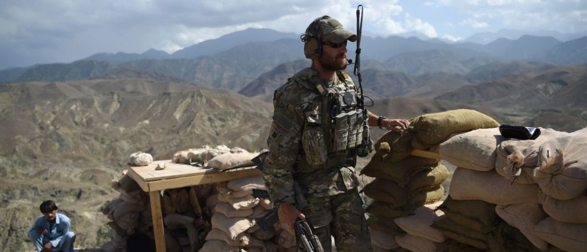 In this photo taken on July 7, 2018, a U.S. Army soldier from NATO and an Afghan Local Police (ALP) look on in a checkpoint during a patrol against Islamic State militants at the Deh Bala district in the eastern province of Nangarhar Province. (Photo by WAKIL KOHSAR / AFP)