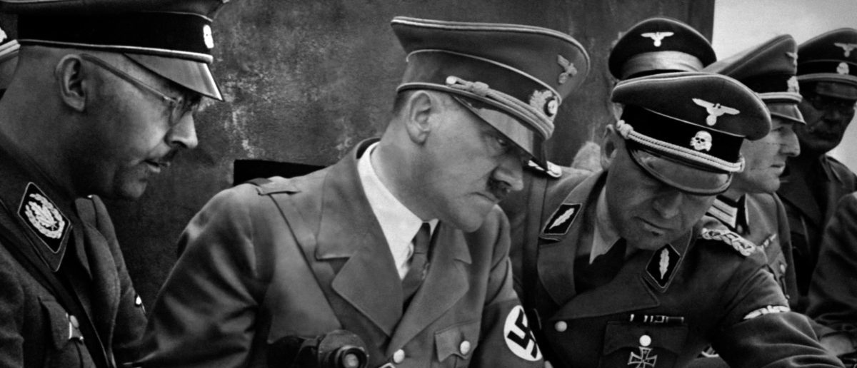 A picture dated 1939 shows German Nazi Chancellor and dictator Adolf Hitler (C) consulting a geographical survey map with his general staff including Heinrich Himmler (L) and Martin Bormann (R) at an unlocated place during World War II. (Photo credit: -/AFP/Getty Images)