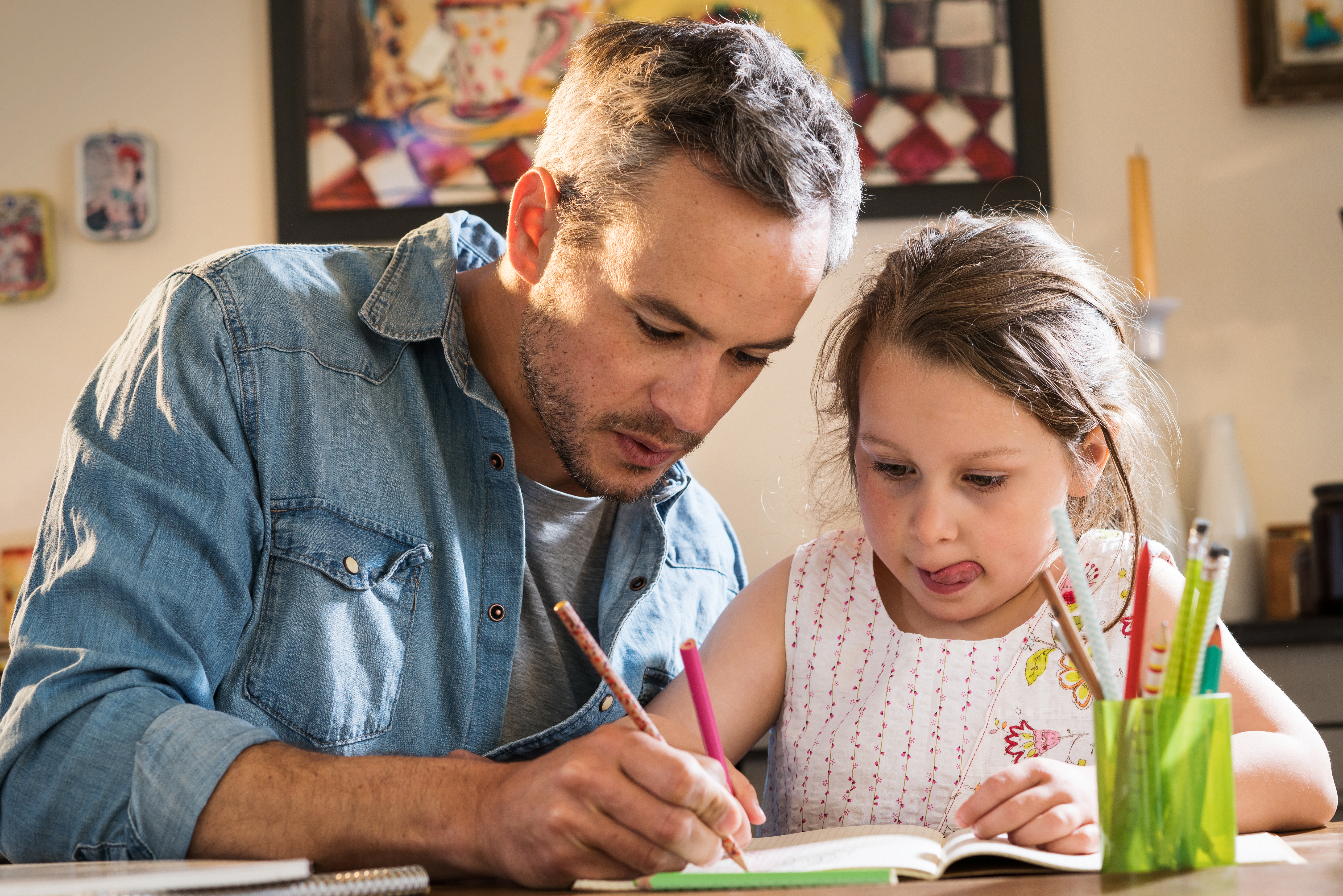 Pictured is a father and his daughter working on homework. SHUTTERSTOCK/ Jack Frog