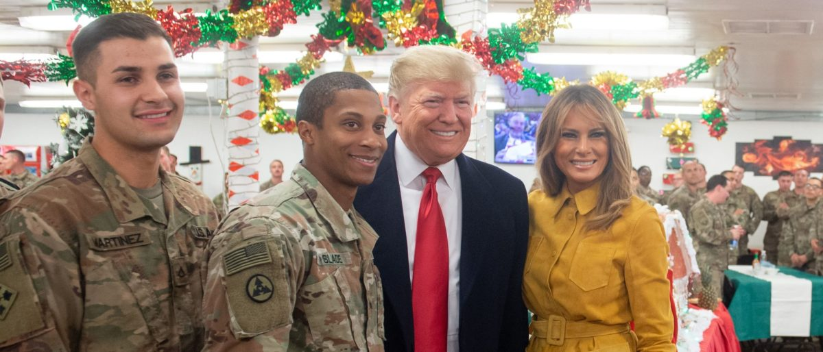 President Donald Trump and first lady Melania Trump take photos with members of the US military during an unannounced trip to Al Asad Air Base in Iraq. (Saul Loeb/AFP/Getty Images)