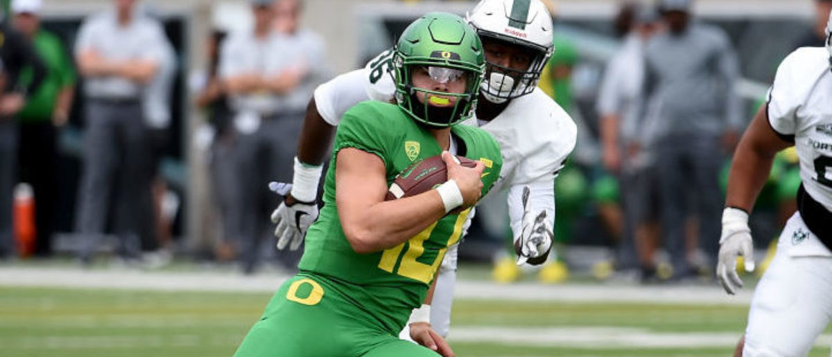 EUGENE, OR - SEPTEMBER 08: Quarterback Justin Herbert #10 of the Oregon Ducks runs with the ball as cornerback Montre Brown #23 and tight end defensive tackle Semise Kofe #95 of the Portland State Vikings give chase during the first quarter of the game at Autzen Stadium on September 8, 2018 in Eugene, Oregon. (Photo by Steve Dykes/Getty Images)