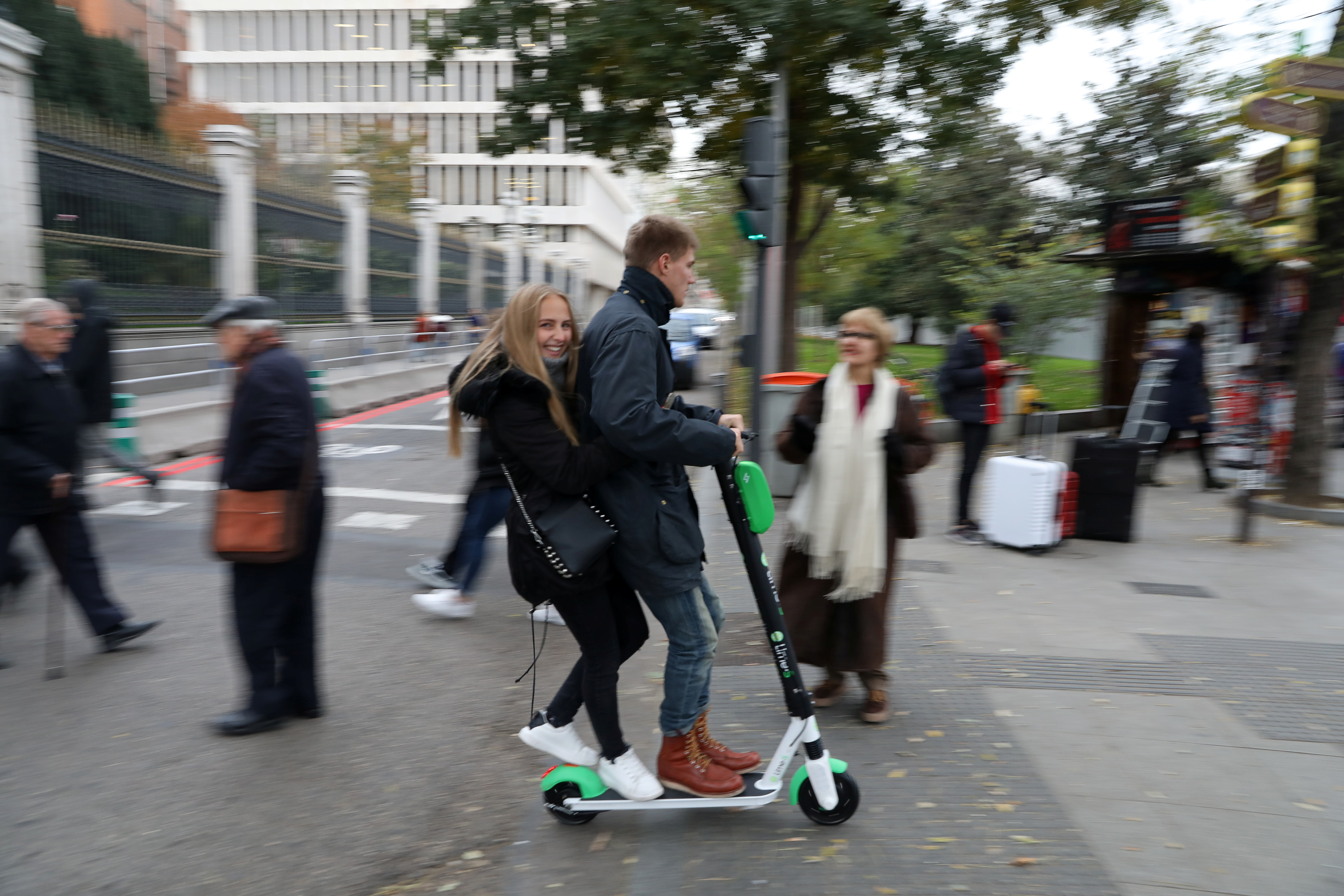 A man and a woman ride a Lime-S, dock-free electric scooter, in Madrid, Spain, November 29, 2018. REUTERS/Susana Vera