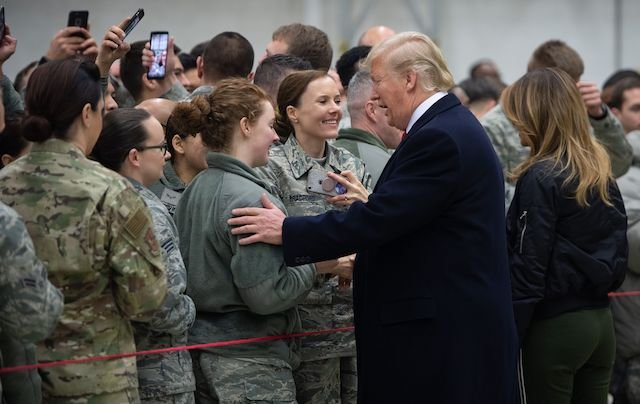 """US President Donald Trump and First Lady Melania Trump greet members of the US military during a stop at Ramstein Air Base in Germany, on December 27, 2018. - President Donald Trump used a lightning visit to Iraq -- his first with US troops in a conflict zone since being elected -- to defend the withdrawal from Syria and to declare an end to America's role as the global """"policeman."""" (Photo credit: SAUL LOEB/AFP/Getty Images)"""
