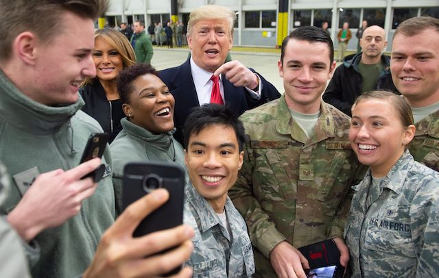 "US President Donald Trump and First Lady Melania Trump greet members of the US military during a stop at Ramstein Air Base in Germany, on December 27, 2018. - President Donald Trump used a lightning visit to Iraq -- his first with US troops in a conflict zone since being elected -- to defend the withdrawal from Syria and to declare an end to America's role as the global ""policeman."" (Photo credit:SAUL LOEB/AFP/Getty Images)"