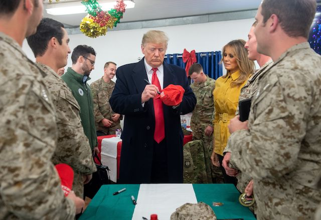 US President Donald Trump signs a hat as First Lady Melania Trump looks on as they greet members of the US military during an unannounced trip to Al Asad Air Base in Iraq on December 26, 2018. - President Donald Trump arrived in Iraq on his first visit to US troops deployed in a war zone since his election two years ago. (Photo credit should read SAUL LOEB/AFP/Getty Images)