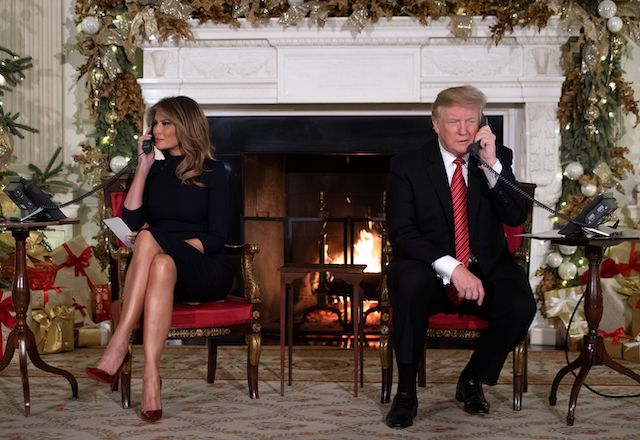 US President Donald Trump and First Lady Melania Trump speak on the telephone as they answers calls from people calling into the NORAD Santa tracker phone line in the State Dining Room of the White House in Washington, DC, on December 24, 2018. (Photo credit: SAUL LOEB/AFP/Getty Images)