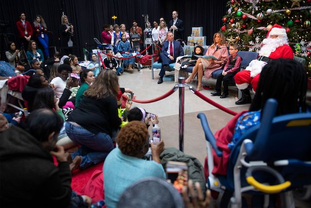 "US First Lady Melania Trump reads the book ""Oliver the Ornament"" as she visits children at Children's National Hospital in Washington, DC, on December 13, 2018. (Photo credit: JIM WATSON/AFP/Getty Images)"