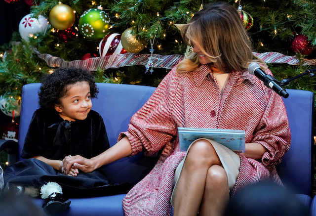 U.S. first lady Melania Trump reaches out to Tearrianna Cooke-Starkey while reading a children's Christmas story during her visit Children's National Health System in Washington, U.S., December 13, 2018. REUTERS/Kevin Lamarque