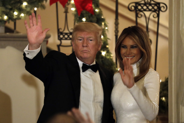 U.S. President Donald Trump and First Lady Melania Trump wave to the guests at the Congressional Ball at White House in Washington on December 15, 2018. (Photo by Yuri Gripas-Pool/Getty Images)
