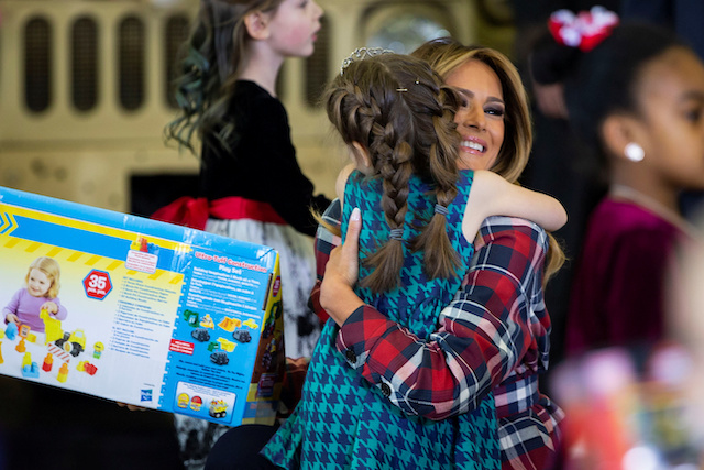 U.S. first lady Melania Trump hugs a young girl as she helps to sort and box toys for the Marine Corps Reserve Toys for Tots campaign at Joint Base Anacostia-Bolling in Washington, U.S., December 11, 2018. REUTERS/Al Drago