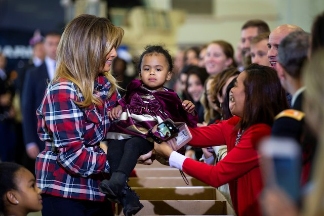 U.S. first lady Melania Trump is handed a young girl during the Marine Corps Reserve Toys for Tots campaign at Joint Base Anacostia-Bolling in Washington, U.S., December 11, 2018. REUTERS/Al Drago