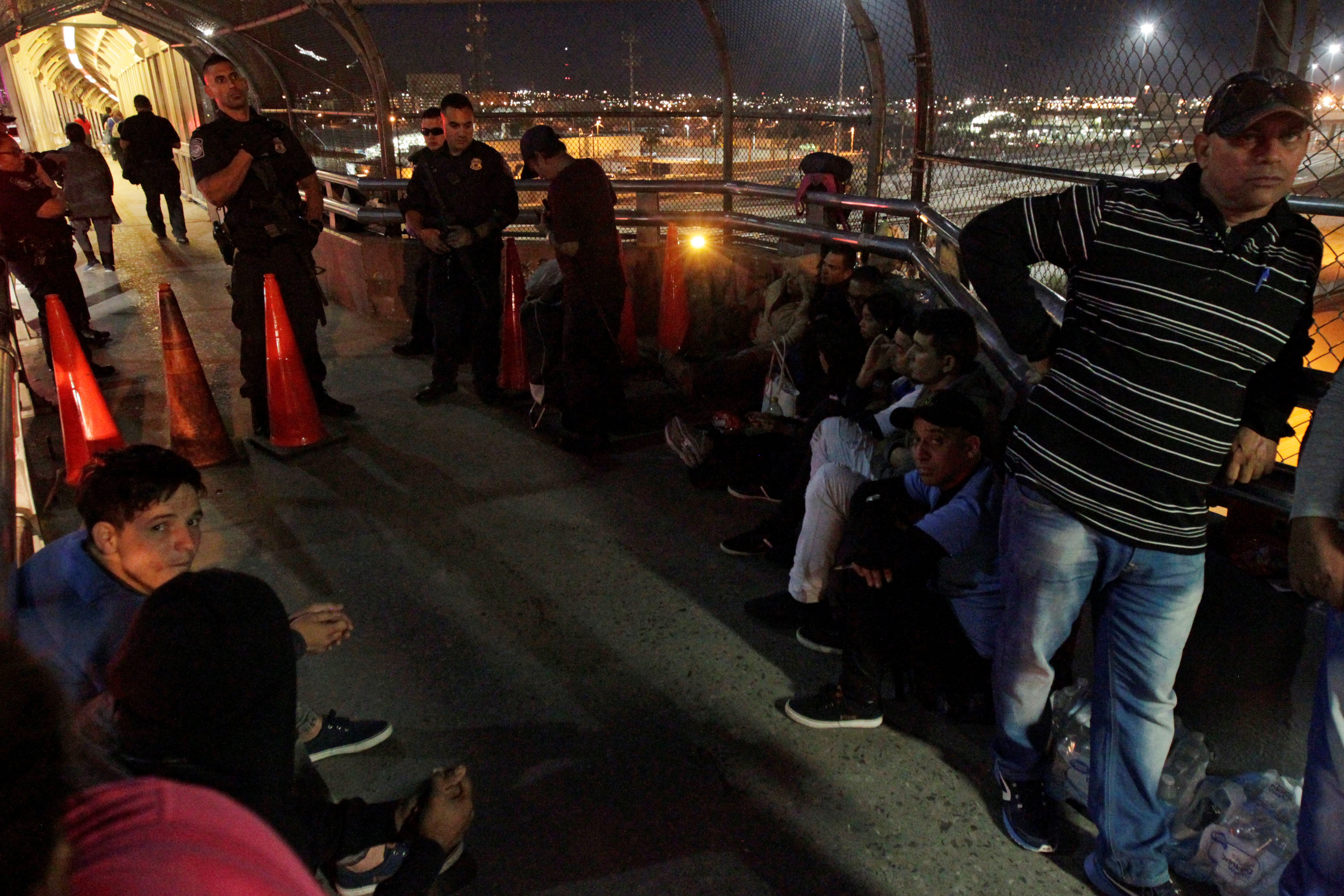 A group of Central Americans and Cubans hoping to apply for asylum wait at the border on an international bridge between Mexico and the U.S., in Ciudad Juarez, Mexico October 25, 2018. REUTERS/Jose Luis Gonzalez