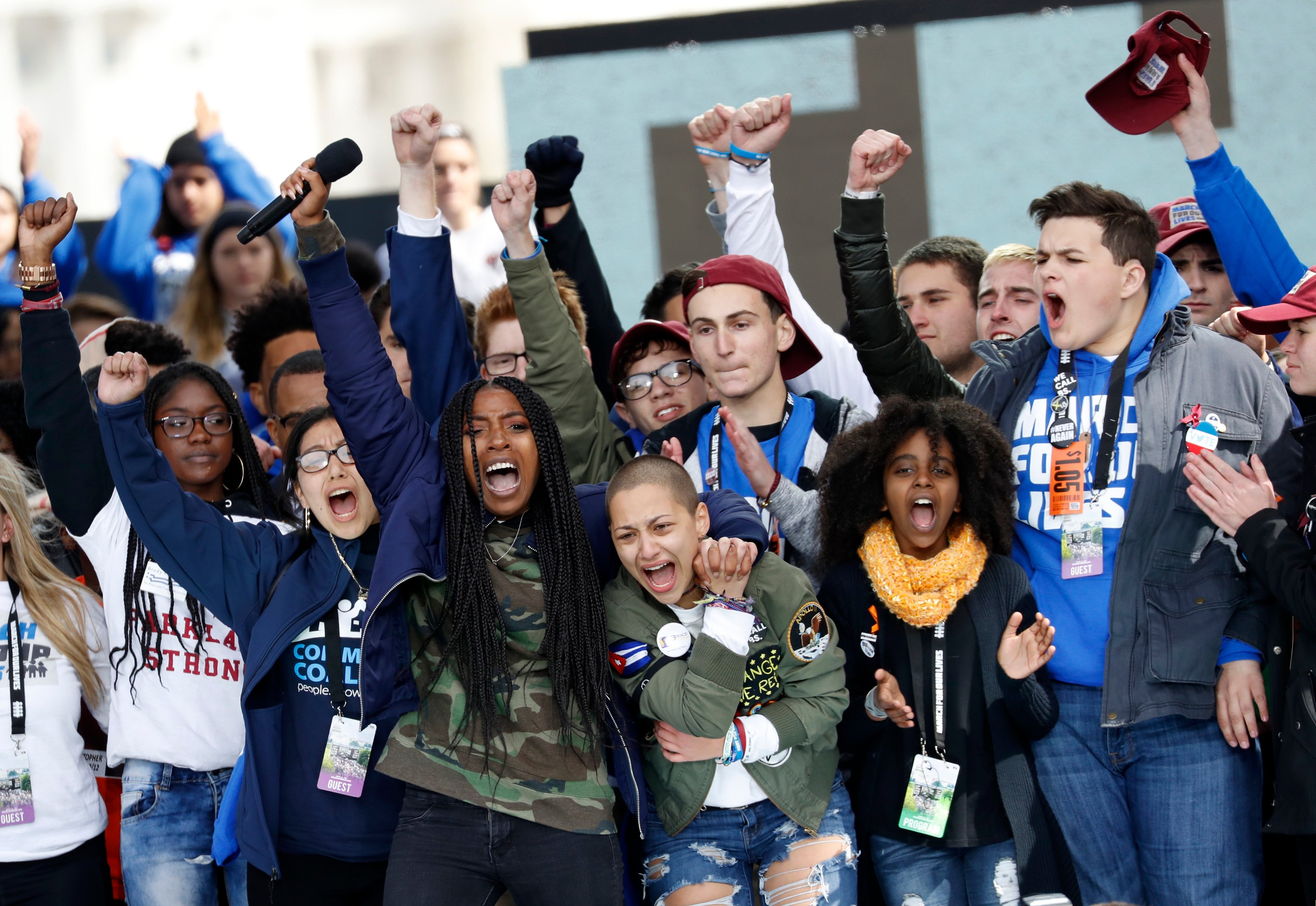 "Students and shooting survivors Tyra Hemans and Emma Gonzalez (3rd from R), from Marjory Stoneman Douglas High School in Parkland, Florida, and 11-year-old Naomi Wadler of Alexandria, Virginia (2nd from R), sing along with other students and shooting survivors at the conclusion of the ""March for Our Lives"" event demanding gun control after recent school shootings at a rally in Washington, U.S., March 24, 2018. REUTERS/Aaron P. Bernstein"