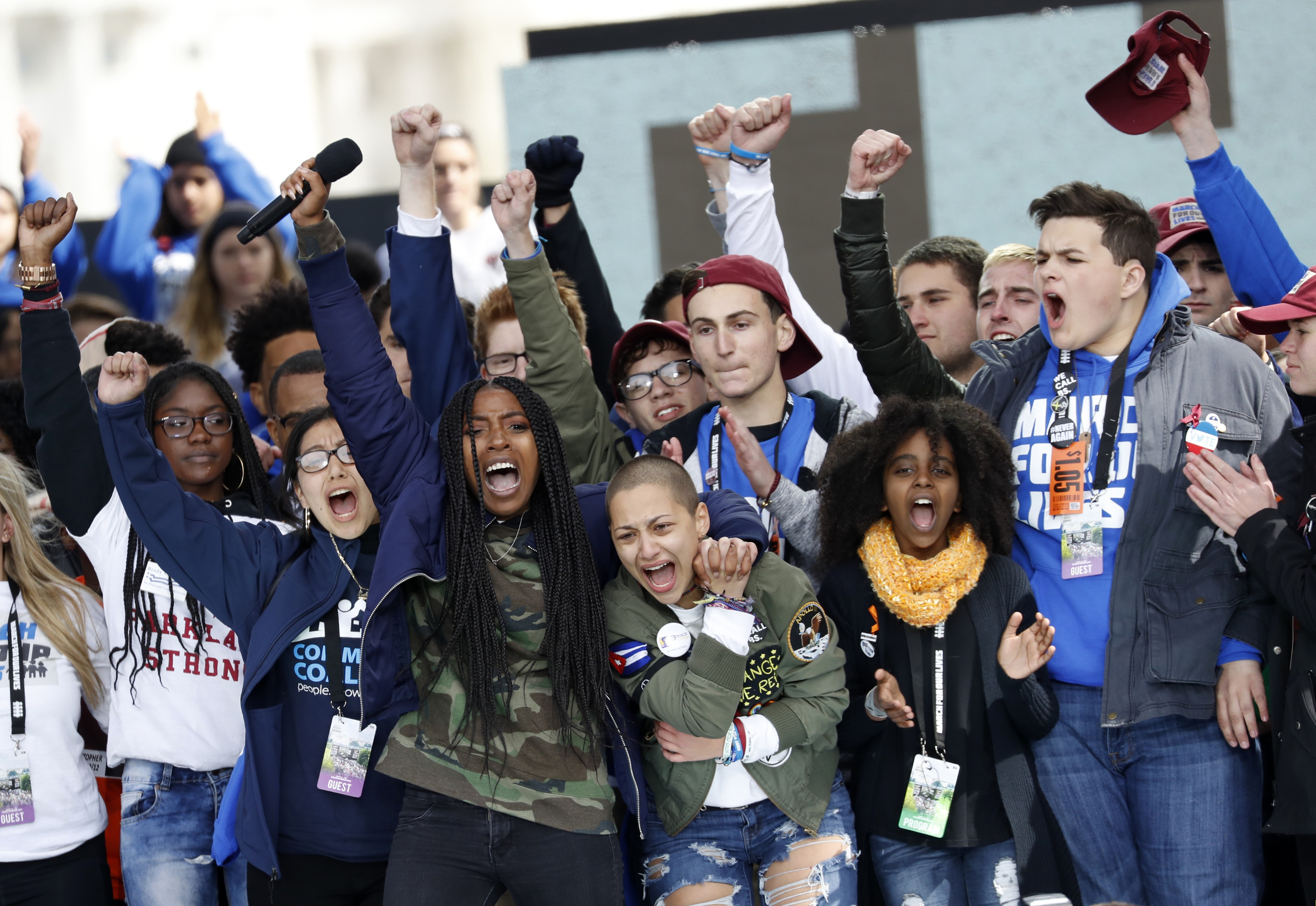 """Students and shooting survivors Tyra Hemans and Emma Gonzalez (3rd from R), from Marjory Stoneman Douglas High School in Parkland, Florida, and 11-year-old Naomi Wadler of Alexandria, Virginia (2nd from R), sing along with other students and shooting survivors at the conclusion of the """"March for Our Lives"""" event. REUTERS/Aaron P. Bernstein"""