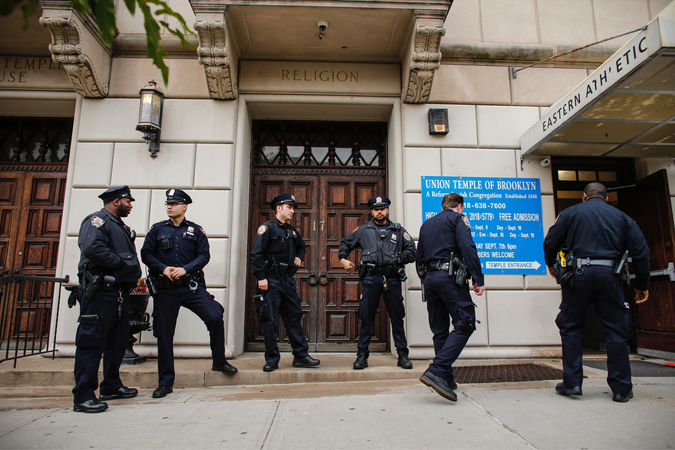 NYPD officers stand guard at the door of the Union Temple of Brooklyn on November 2, 2018 in New York City. - New York police were investigating anti-Semitic graffiti found inside a Brooklyn synagogue that forced the cancellation of a political event less than a week after the worst anti-Semitic attack in modern US history. (KENA BETANCUR/AFP/Getty Images)