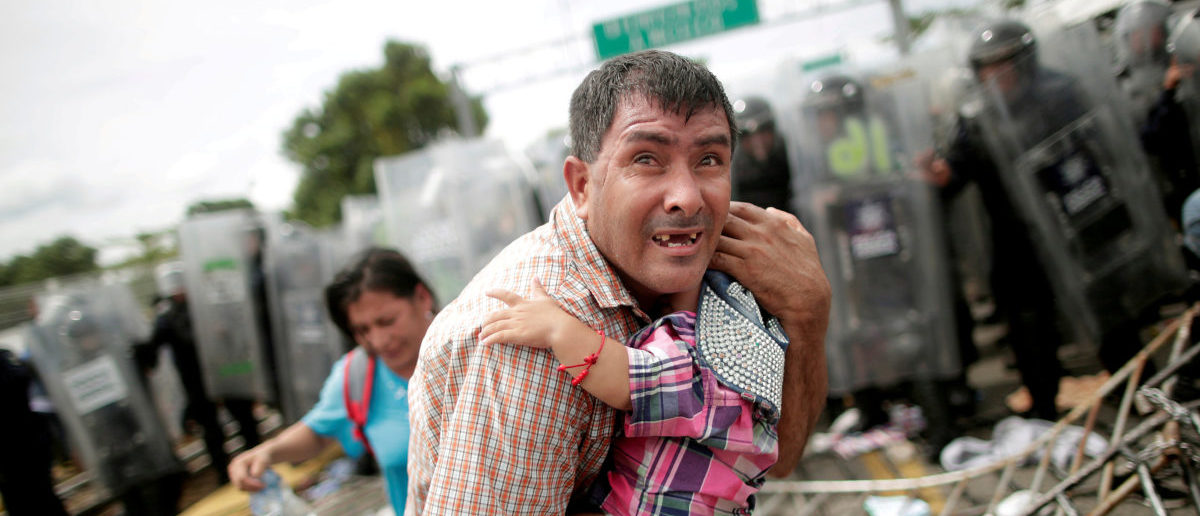 "A Honduran migrant protects his child after fellow migrants, part of a caravan trying to reach the U.S., stormed a border checkpoint in Guatemala, in Ciudad Hidalgo, Mexico, October 19, 2018. Reuters photographer Ueslei Marcelino: ""The migrants had already broken through the first police barricade on the Guatemalan side of the bridge. After a while, they moved towards the second barricade on the Mexican side. The push by the migrants to enter Mexico had eased and suddenly women and children formed a line and started to walk towards the police. There was a bit of pushing and shoving, and then things started to get increasingly chaotic. It was a march that turned into a protest and ended up in confusion. Of course, it affected me. I'm also a father of a nine-year-old girl. It was impossible not to think about being that father caught up in that panicked situation. After taking the photo, I took others of families coming out of the restrictive cordon created by police. The confusion was brought under control after gas was used to disperse them, and the migrants were pushed back to the Guatemalan side."" REUTERS/Ueslei Marcelino"