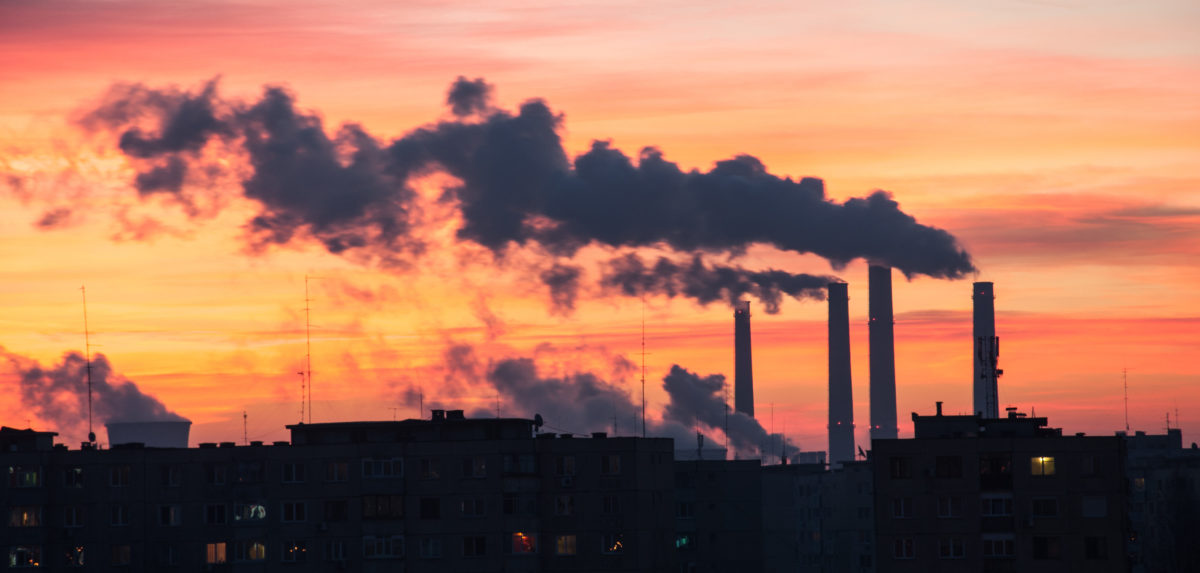 Power Plant emissions seen above residential blocks from a city during sunrise. Shutterstock