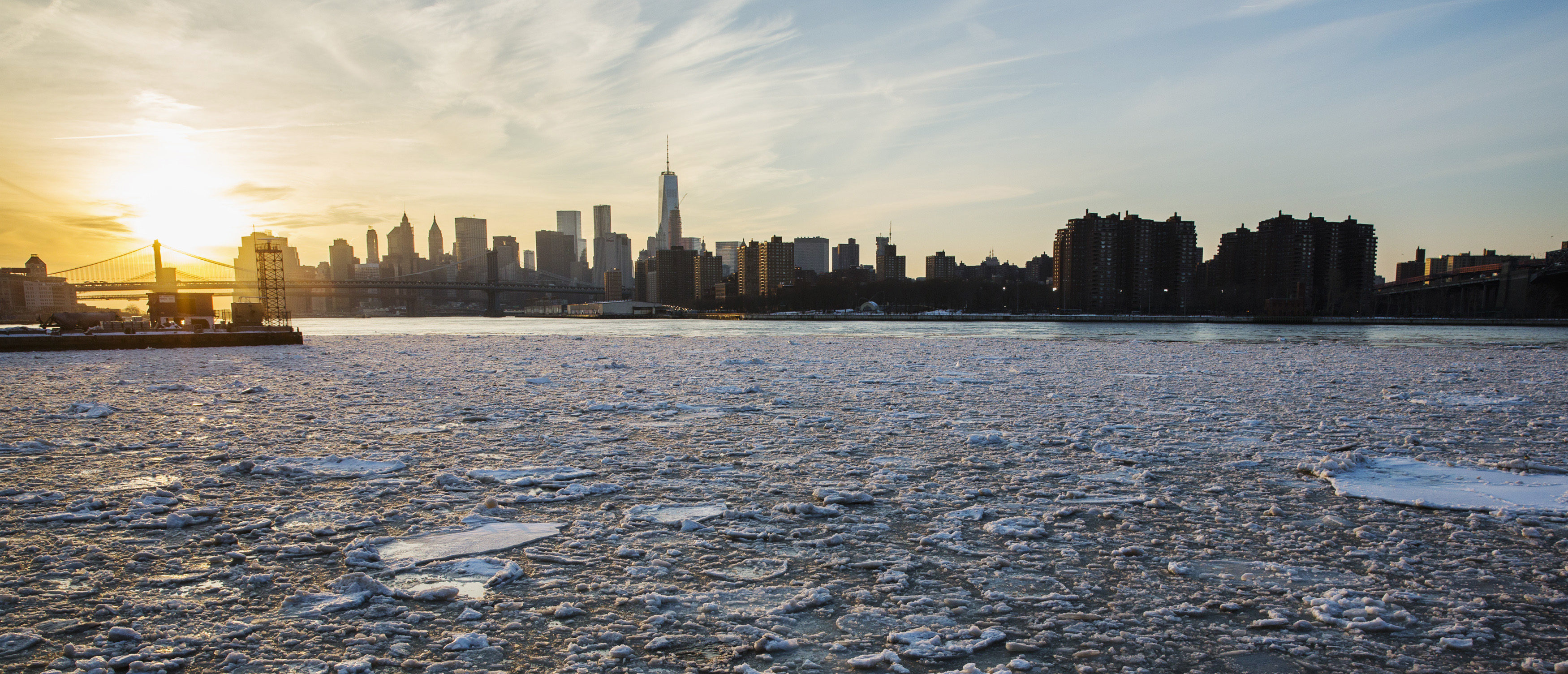The sun sets behind the Manhattan skyline as ice floats down the East River in New York February 25, 2015. REUTERS/Lucas Jackson.