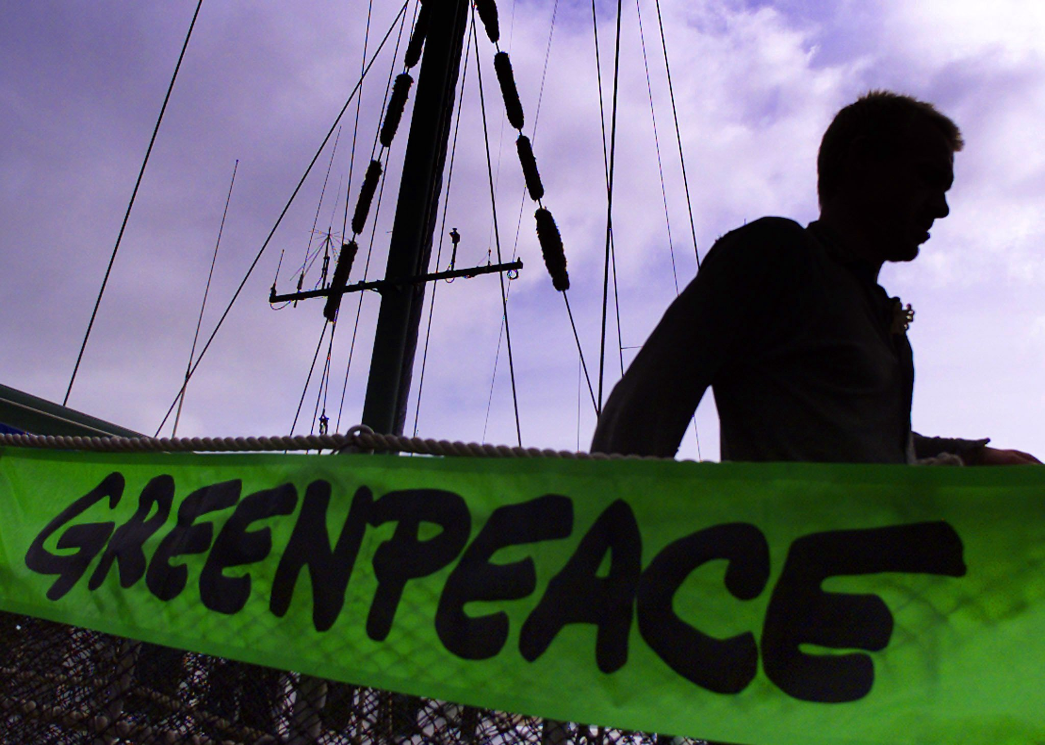 CREW MEMBER OF GREENPEACE SHIP RAINBOW WARRIOR WALKS PAST BANNER WHILEDOCKED IN DUBLIN.