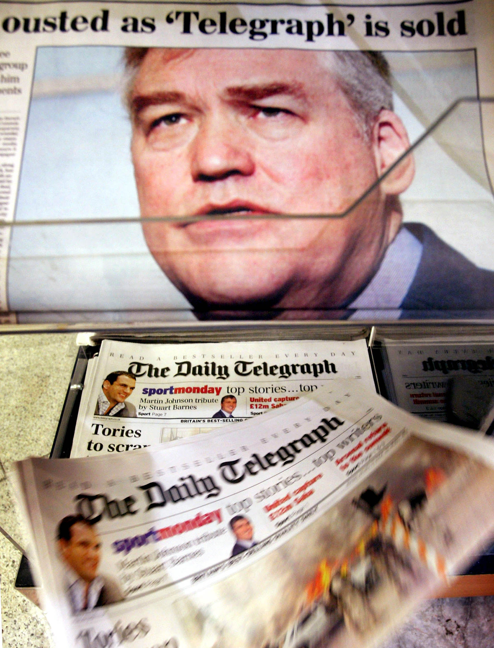 A photograph of publishing magnate Conrad Black is seen on a British newspaper as it carries the story of the bid to buy Black's interest in Toronto-based Hollinger International by billionaire tycoons David and Frederick Barclay, in central London, January 19, 2004. Black said he would sell his controlling stake in the company, which owns the Daily and Sunday Telegraph and Chicago Sun-Times newspapers, to the brothers one day after the company sued him and removed him as chairman. REUTERS/Peter Macdiarmid PKM/ASA/JV - RP4DRIHBNYAA