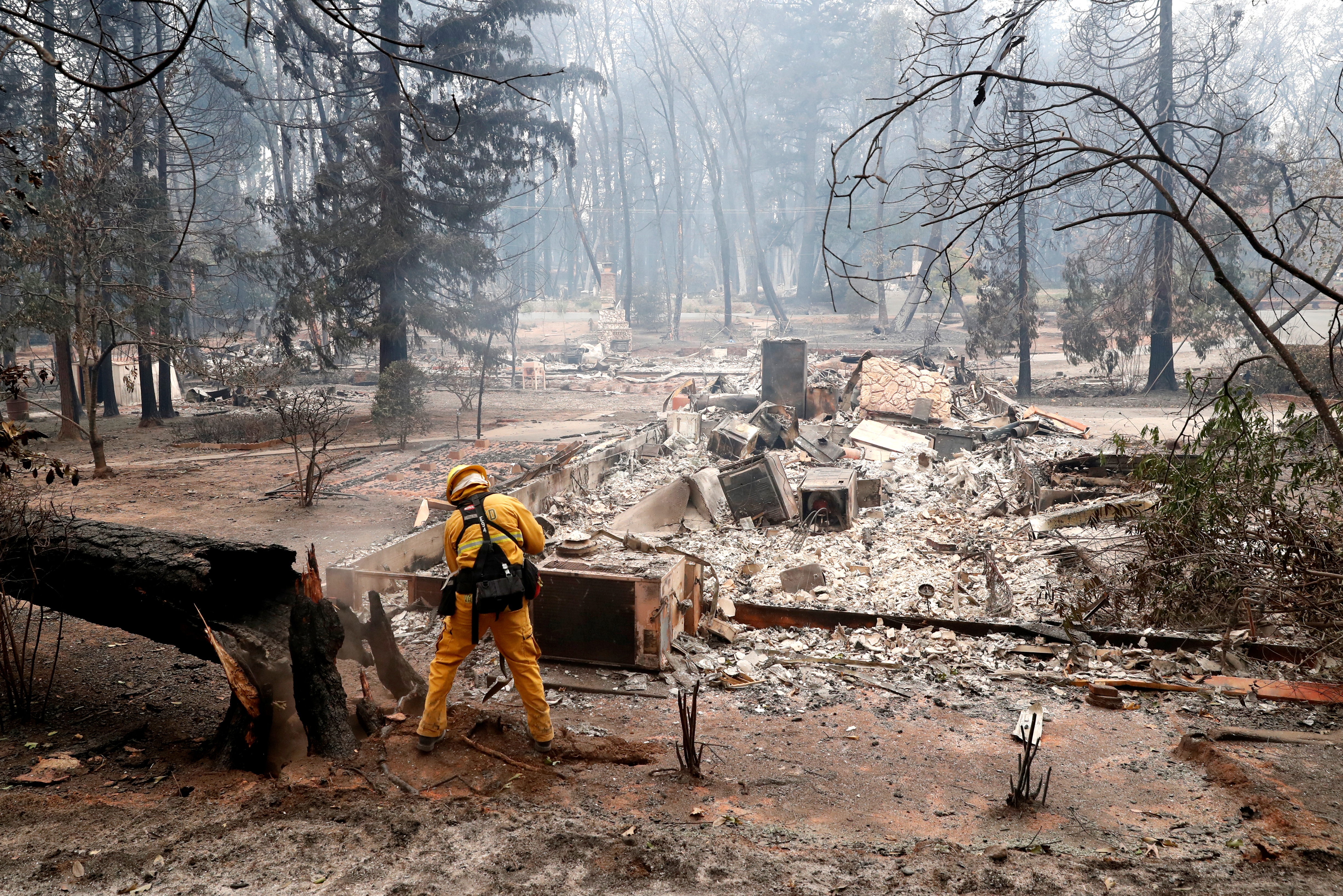 A firefighter extinguishes a hot spot in a neighbourhood destroyed by the Camp Fire in Paradise