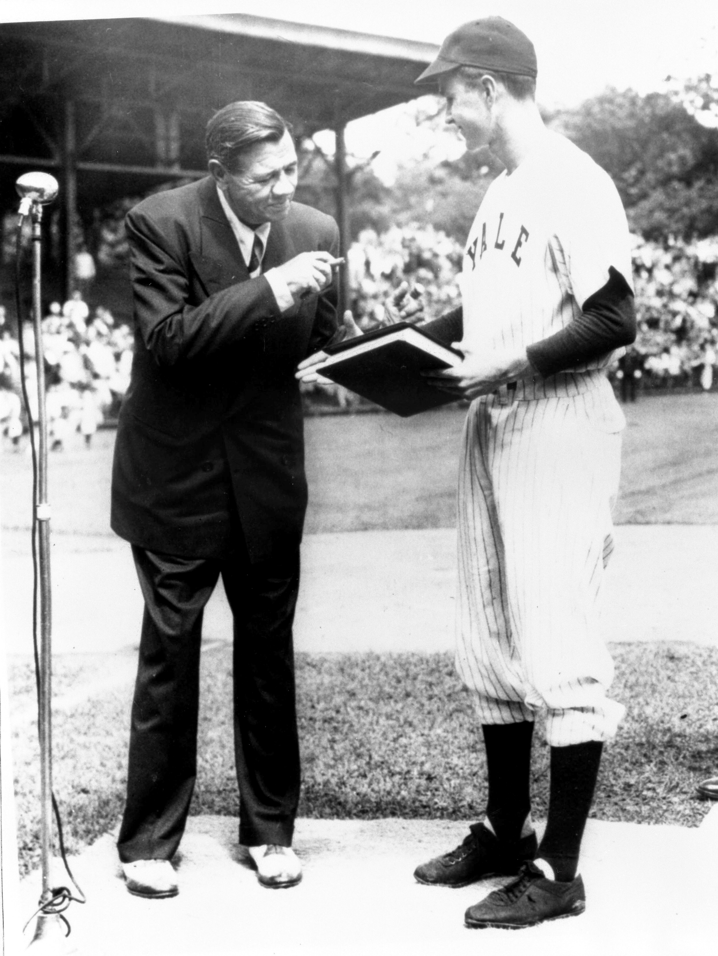 "On behalf of Yale University, baseball captain George Bush accepts ""The Babe Ruth Story"" autobiography from Babe Ruth in this 1948 handout photo obtained by Reuters November 30, 2012. George Bush Presidential Library and Museum/Handout via REUTERS/File Photo"