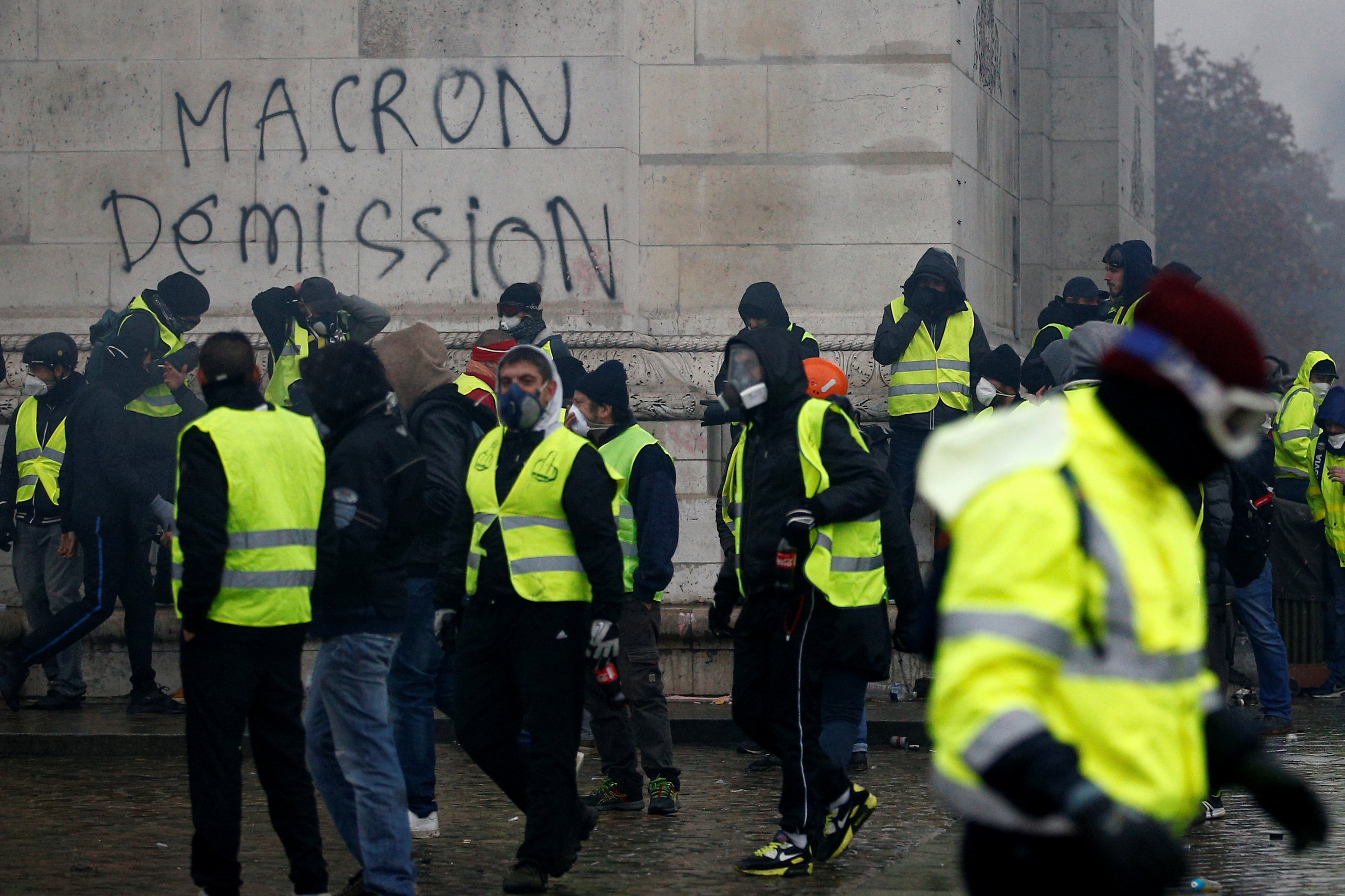 "The message ""Macron Resign"" is seen on the Arc de Triomphe as protesters wearing yellow vests, a symbol of a drivers' protest against higher diesel taxes, demonstrate at the Place de l'Etoile in Paris"