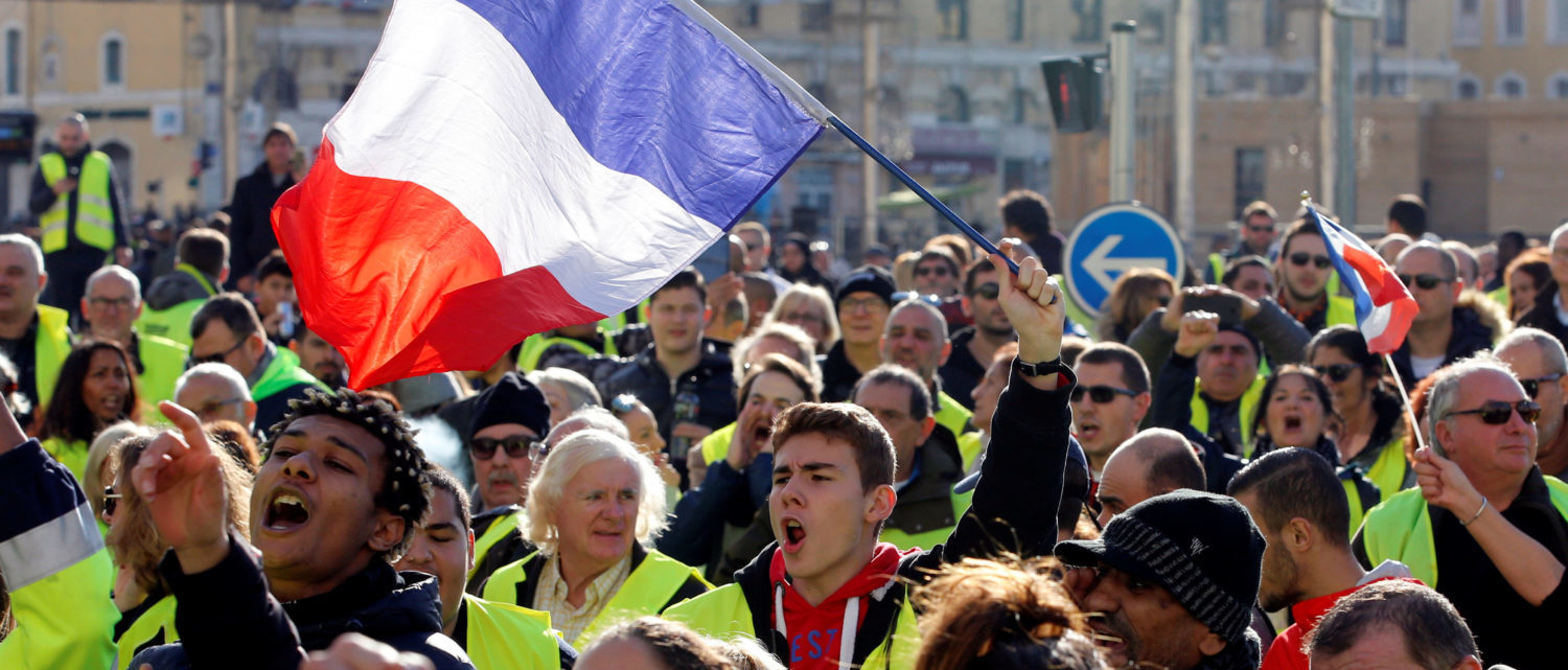 People wearing yellow vests, a symbol of a French drivers' protest against higher diesel fuel prices, wave French flags as they demonstrate in Marseille, France, December 1, 2018. REUTERS/Jean-Paul Pelissier.