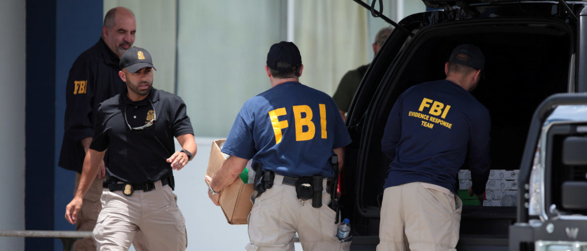 Federal Bureau of Investigation (FBI) personnel load boxes into a car in a search and seizure, July 19, 2017. REUTERS/Alvin Baez