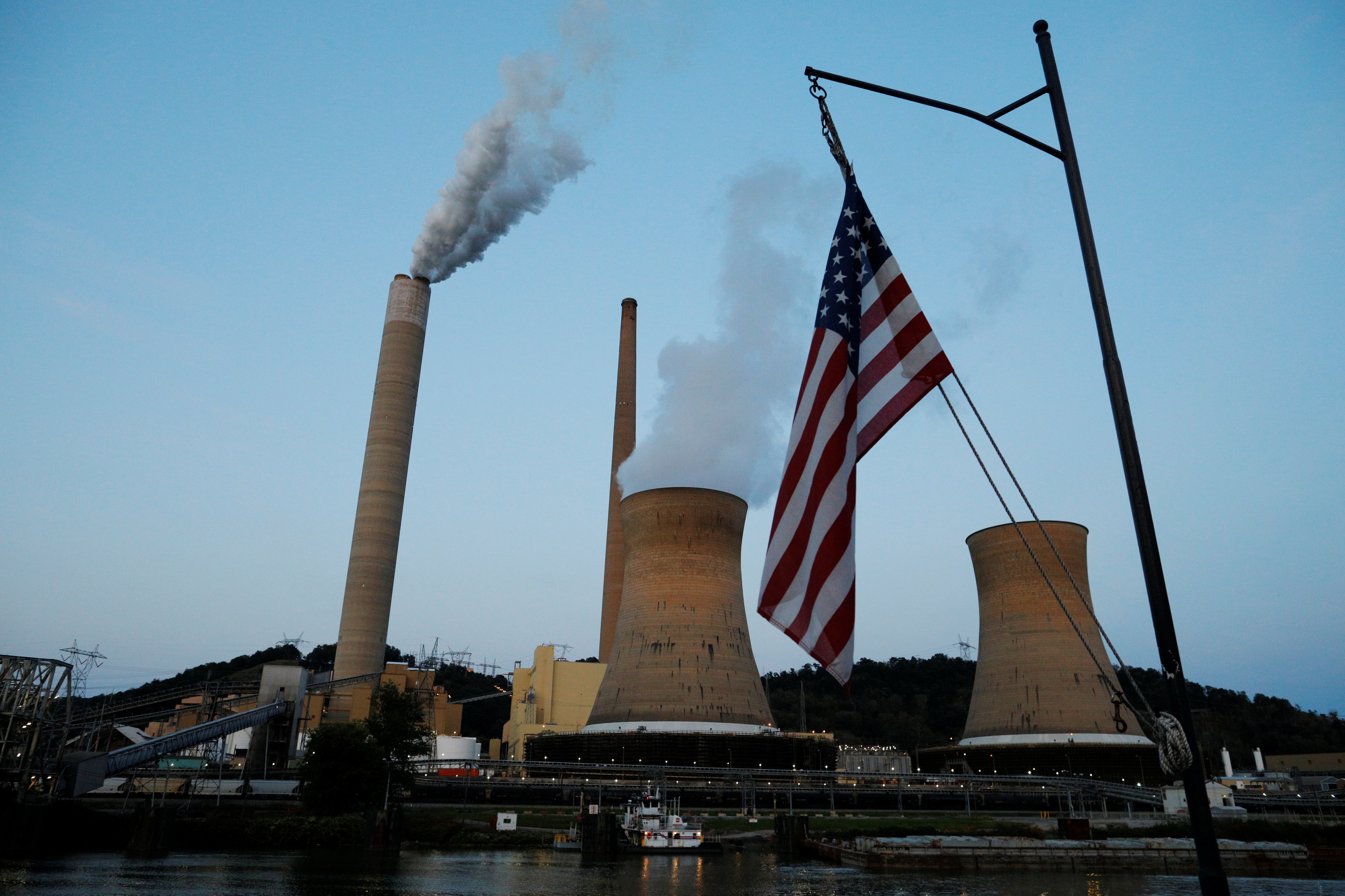 The U.S. flag flies on Campbell Transportation's towboat M.K. McNally as it passes Mitchell Power Plant on the Ohio River in Moundsville