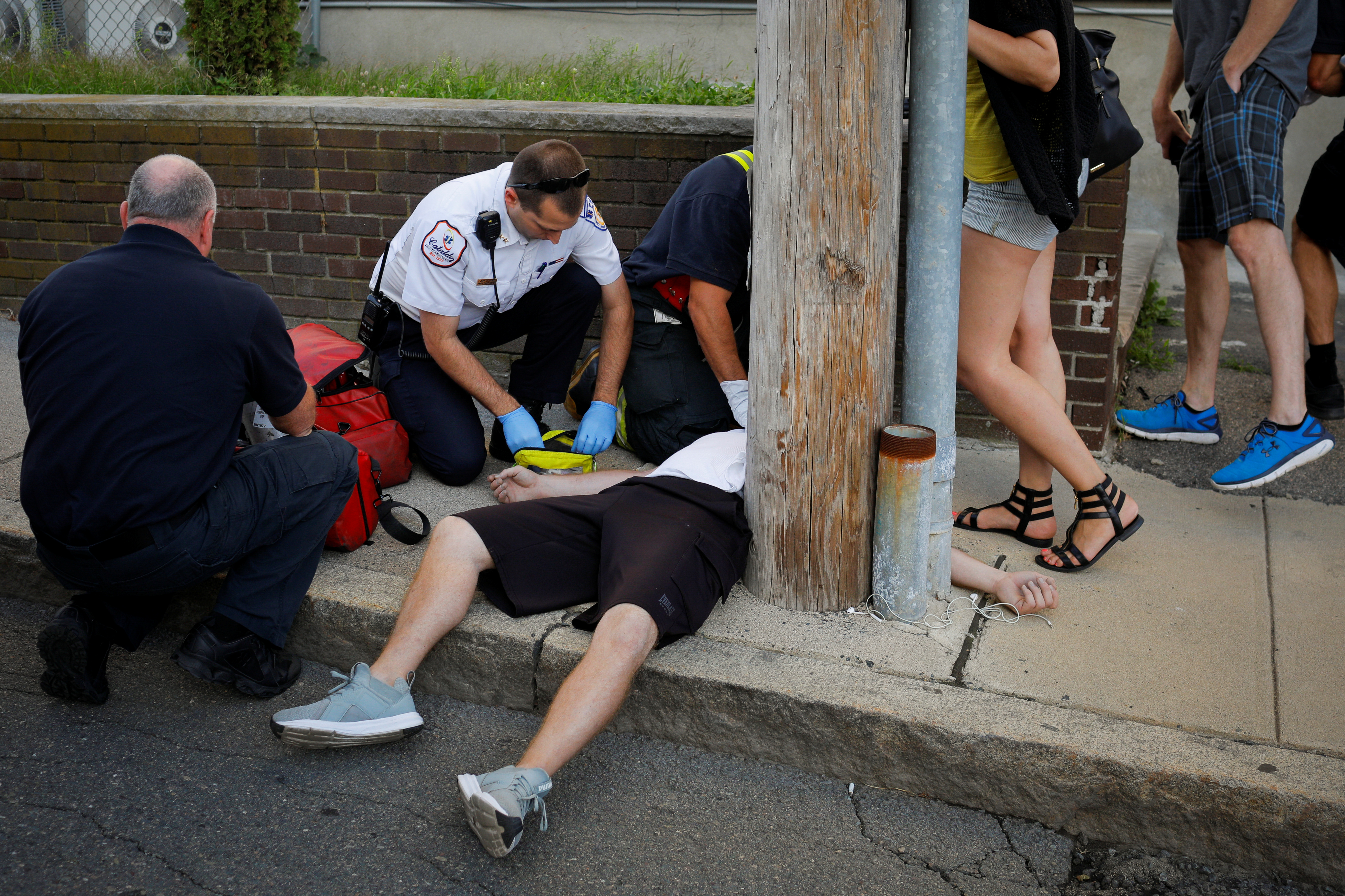 Cataldo Ambulance medics and other first responders revive a man who was found unresponsive and not breathing after an opioid overdose on a sidewalk in the Boston suburb of Everett, Massachusetts, U.S., August 23, 2017. REUTERS/Brian Snyder