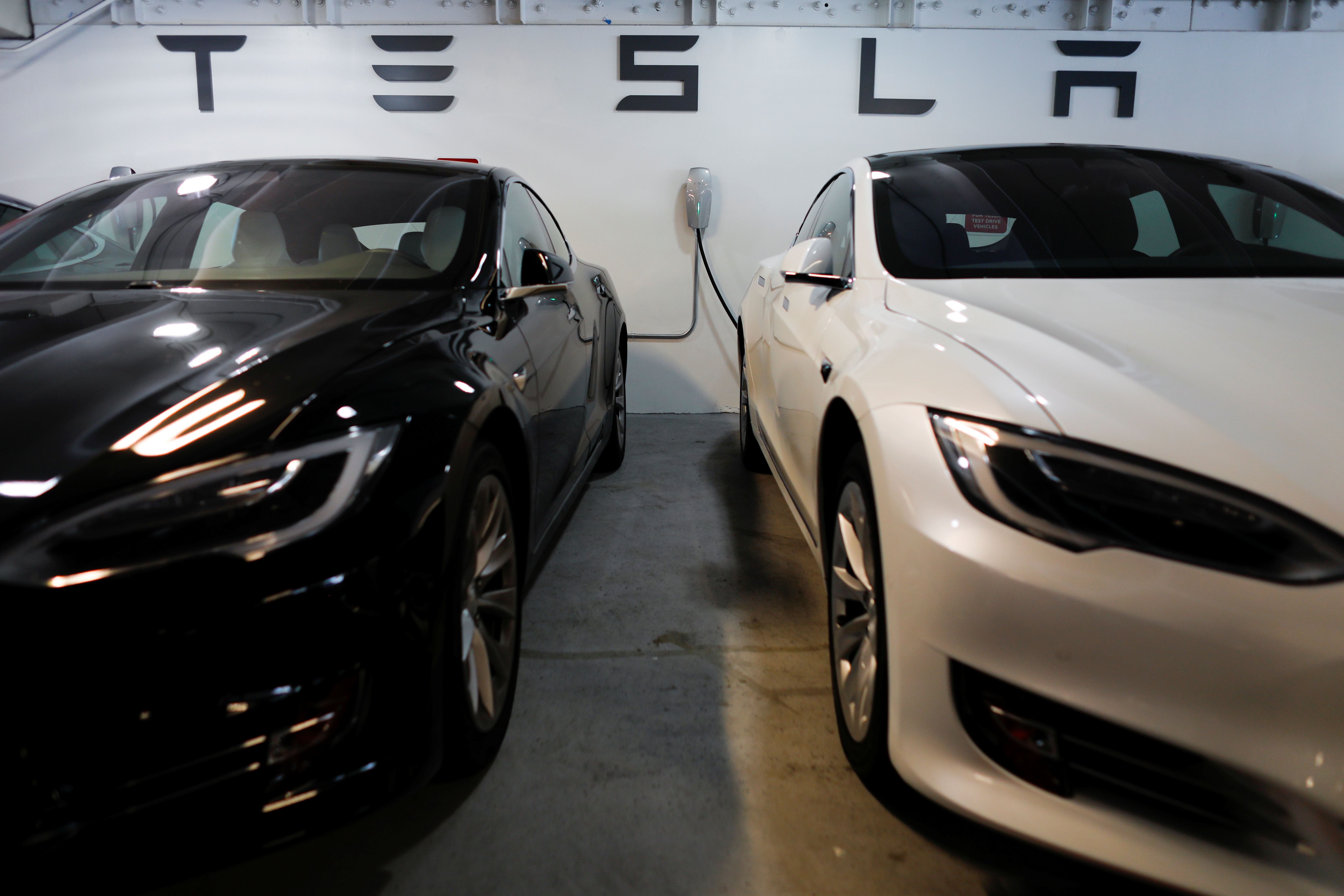 Tesla Model 3s are shown charging in an underground parking lot next to a Tesla store in San Diego,California, U.S., May 30, 2018. REUTERS/Mike Blake.