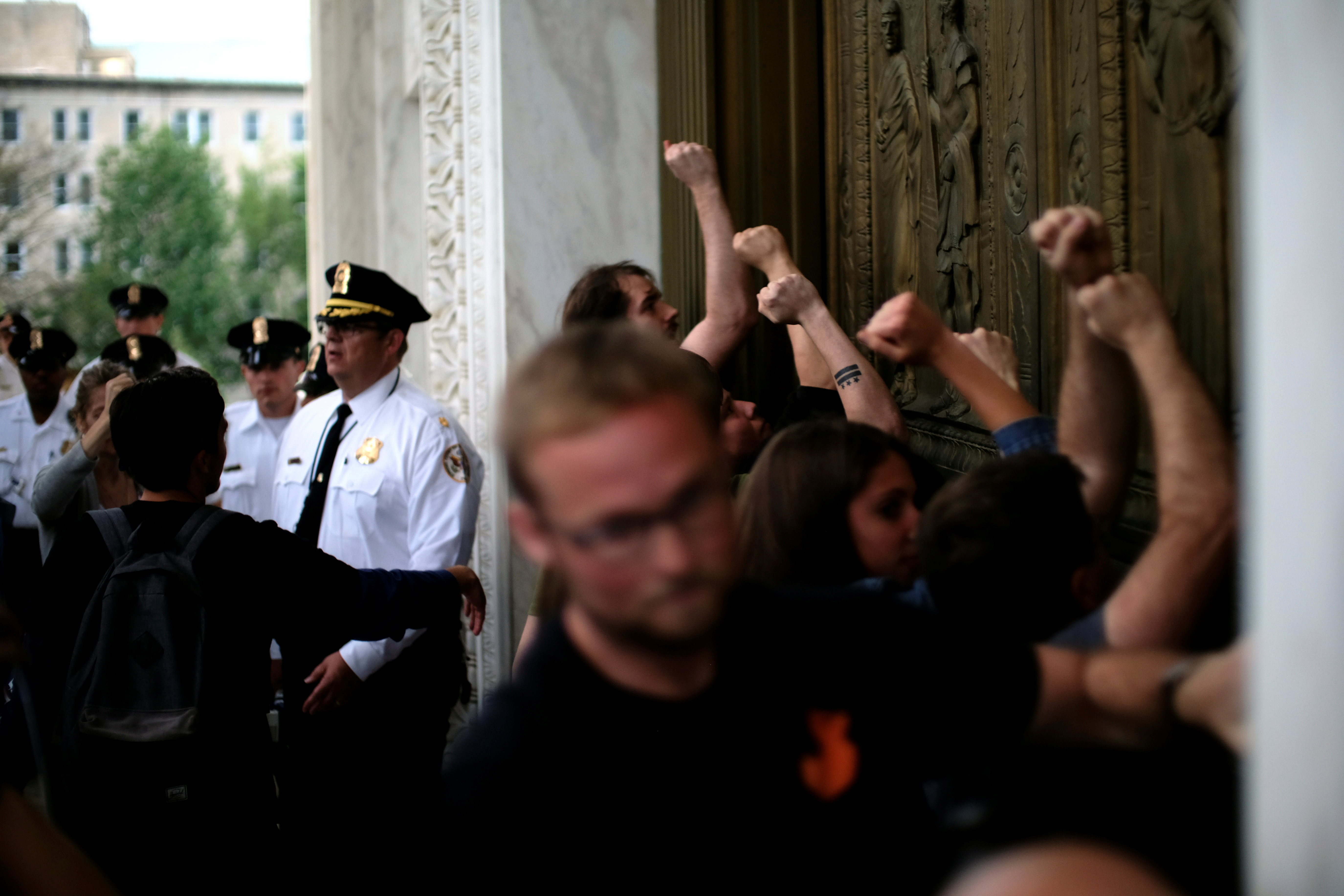 Protesters bang on the doors of the U.S. Supreme Court after storming the steps as Brett Kavanaugh is sworn in as an Associate Justice of the court in Washington, U.S., October 6, 2018. REUTERS/James Lawler Duggan