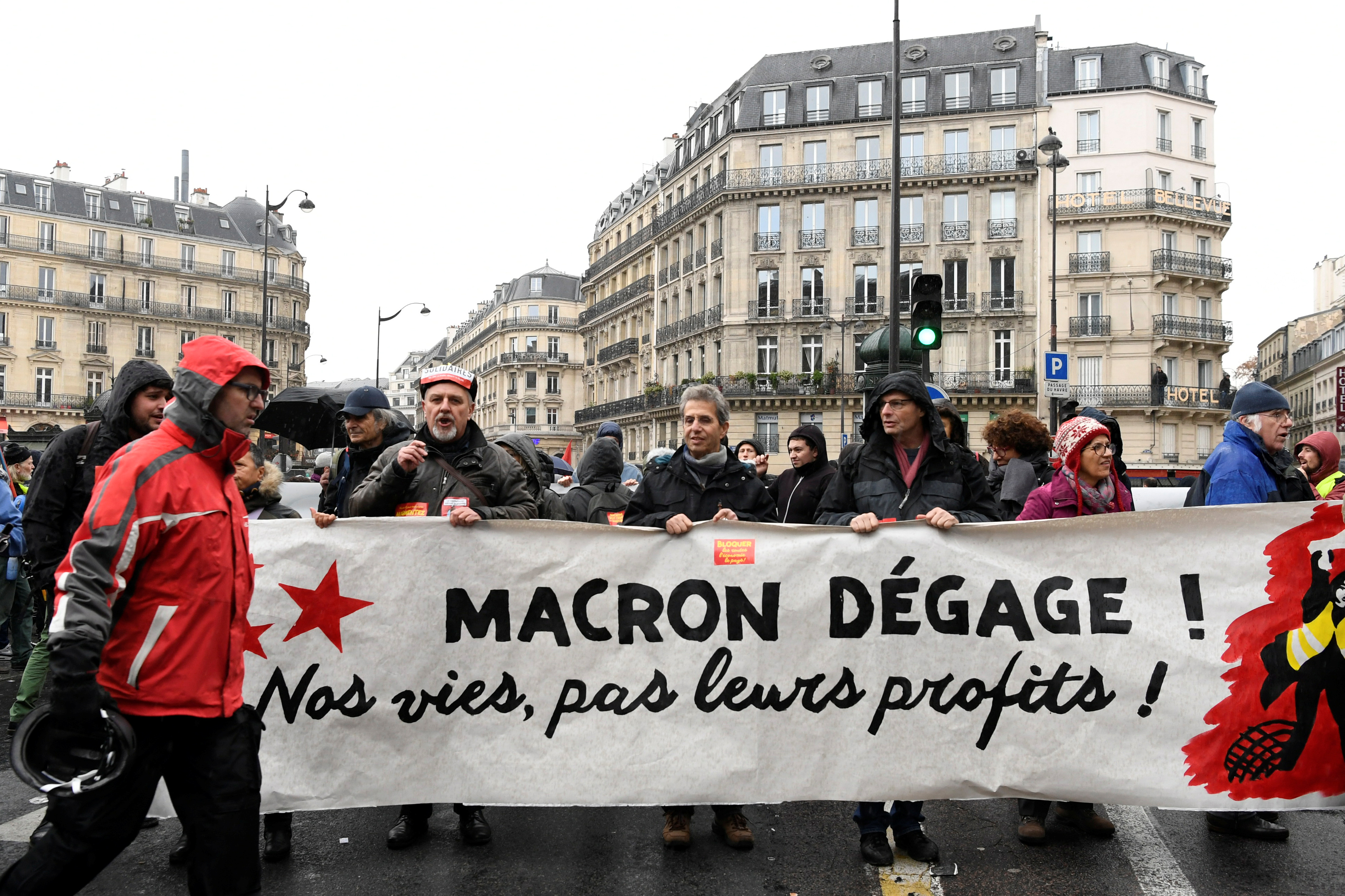 "People hold a banner which reads ""Macron get out, our lives, not our profits"" as they demonstrate in a street during a national day of protest by the ""yellow vests"" movement in Paris"