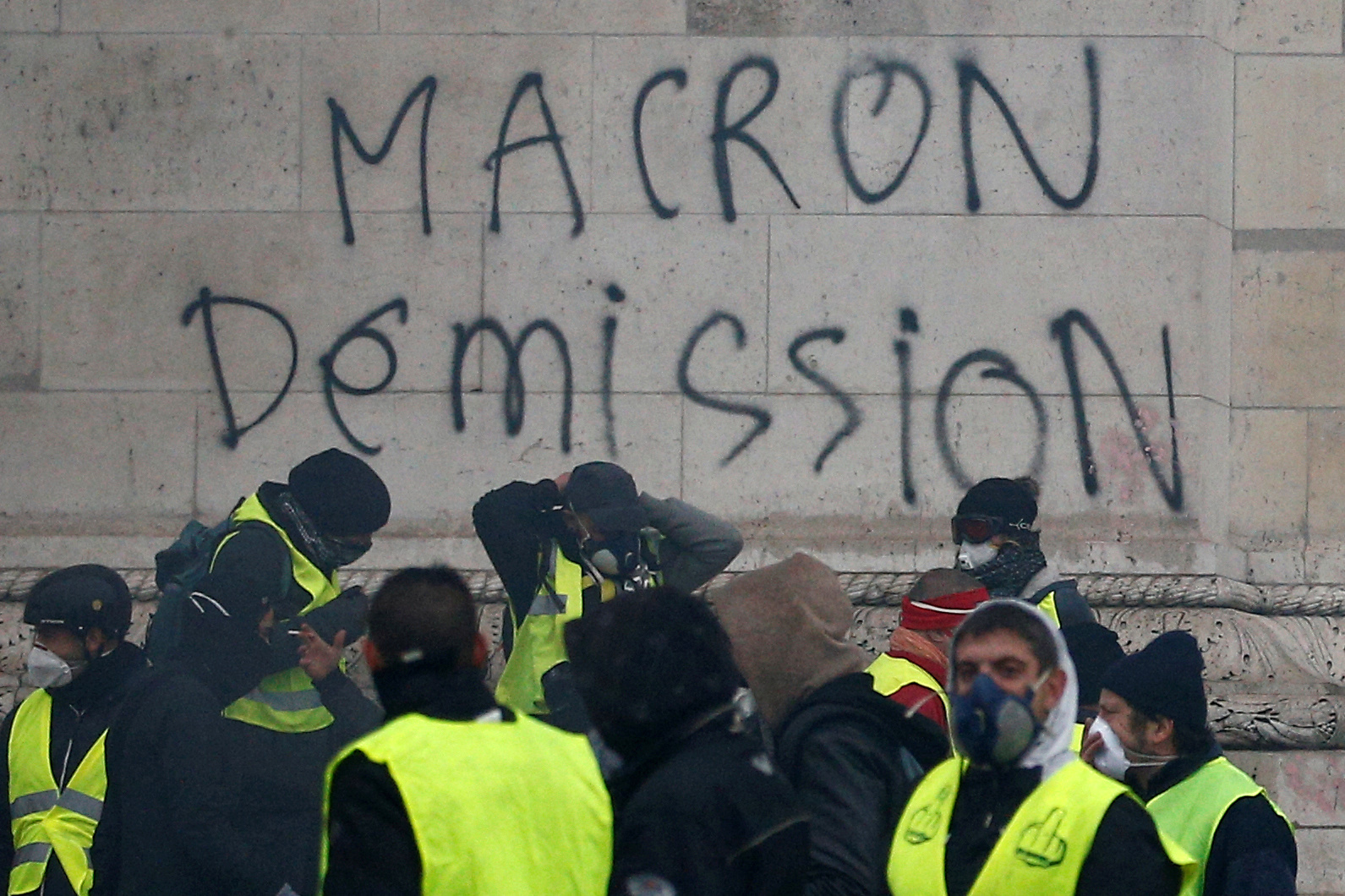 "FILE PHOTO: The message ""Macron Resign"" is seen on the Arc de Triomphe as protesters wearing yellow vests, a symbol of a drivers' protest against higher diesel taxes, demonstrate at the Place de l'Etoile in Paris"