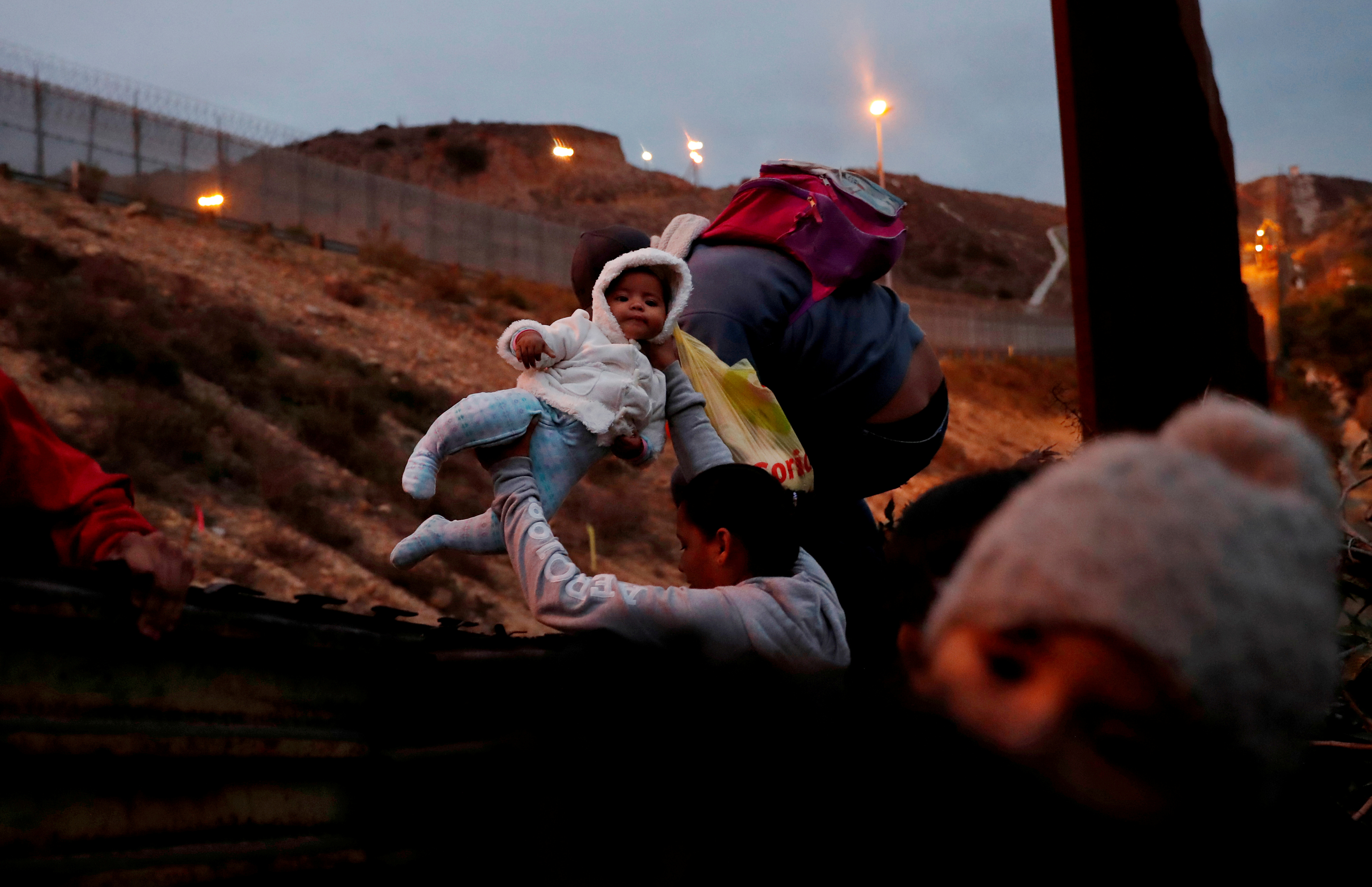 "Honduran migrants, part of a caravan of migrants from Central America traveling with the intention of reaching the U.S. jump over a border fence into the U.S. from Tijuana, Mexico December 14, 2018. Reuters photographer Leah Millis: ""A group of Honduran families had arrived at the beach earlier in the day to cross into the U.S. but found the two possible spots were impassable. So they turned around and walked for another hour to get to this spot, they were really determined. There were several babies in the group and the day had been so long and trying for them that they were asleep in their parent's arms. It was only until they were being passed over the fence that they woke up. This baby stayed quite calm during the process. Border Patrol picked them up quickly, which is something they wanted so they could apply for asylum."" REUTERS/Leah Millis"