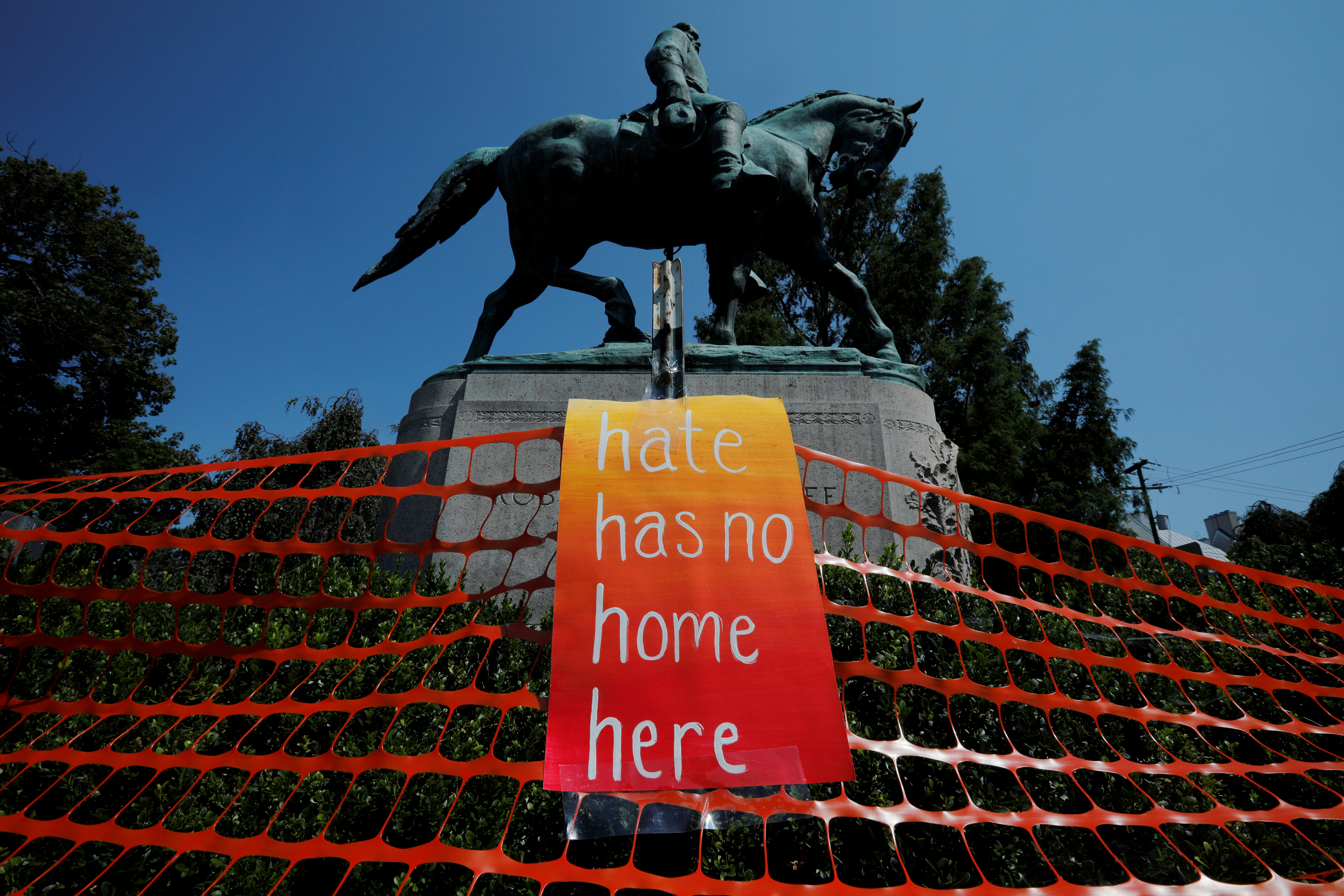 "A sign reading ""Hate Has No Home Here"" hangs by the statue of Civil War Confederate General Robert E. Lee, ahead of the one year anniversary of 2017 Charlottesville ""Unite the Right"" protests, in Charlottesville, Virginia, U.S., August 10, 2018. REUTERS/Brian Snyder"