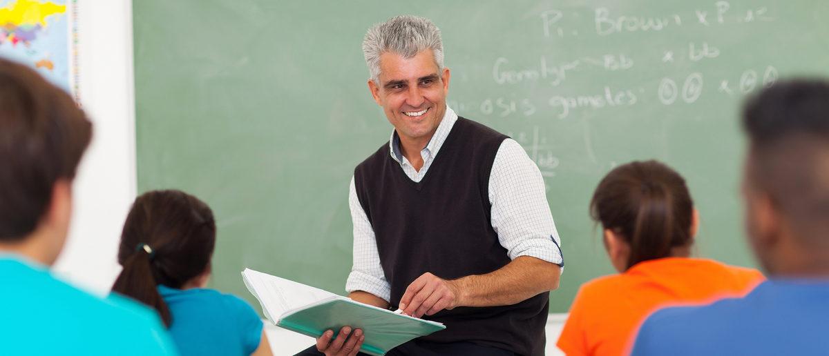 A high school teacher in front of his class. (Shutterstock/michaeljung)