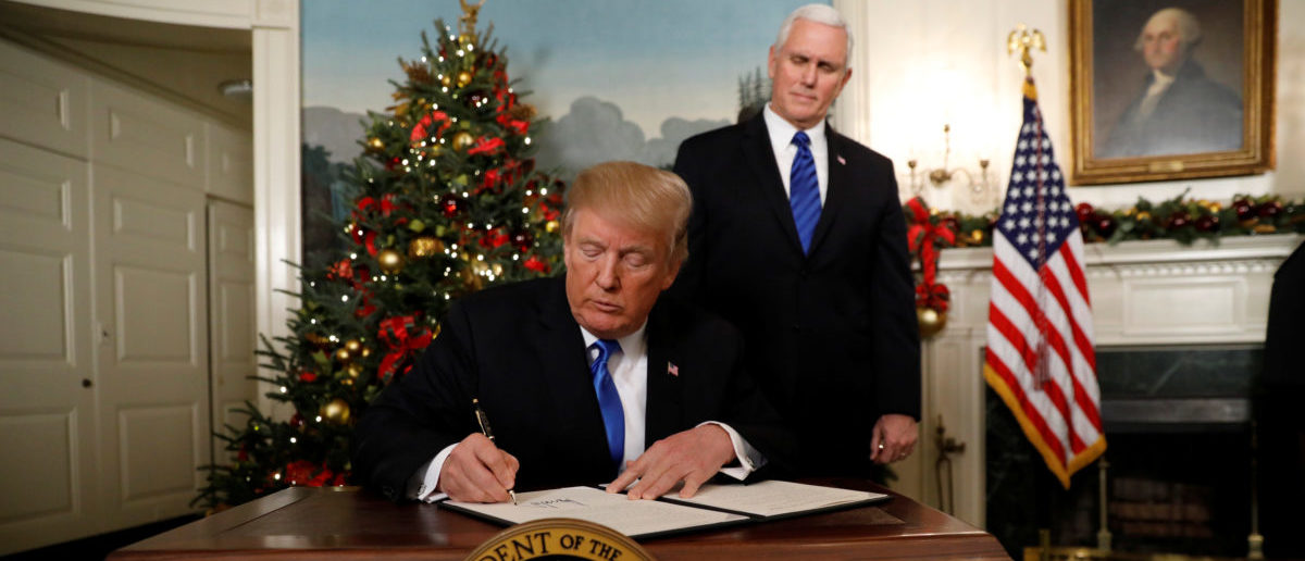 With Vice Pence Mike Pence looking on, U.S. President Donald Trump signs an executive order after he announced the U.S. would recognize Jerusalem as the capital of Israel, in the Diplomatic Reception Room of the White House in Washington, U.S., December 6, 2017. REUTERS/Kevin Lamarque