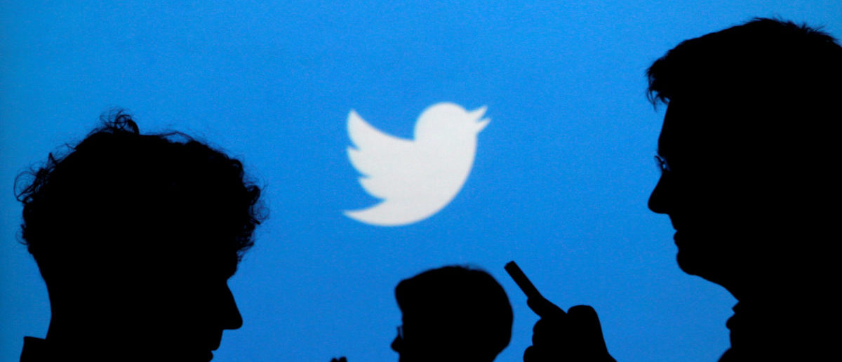 People holding mobile phones are silhouetted against a backdrop projected with the Twitter logo in this illustration picture taken in Warsaw September 27, 2013. REUTERS/Kacper Pempel/File Photo