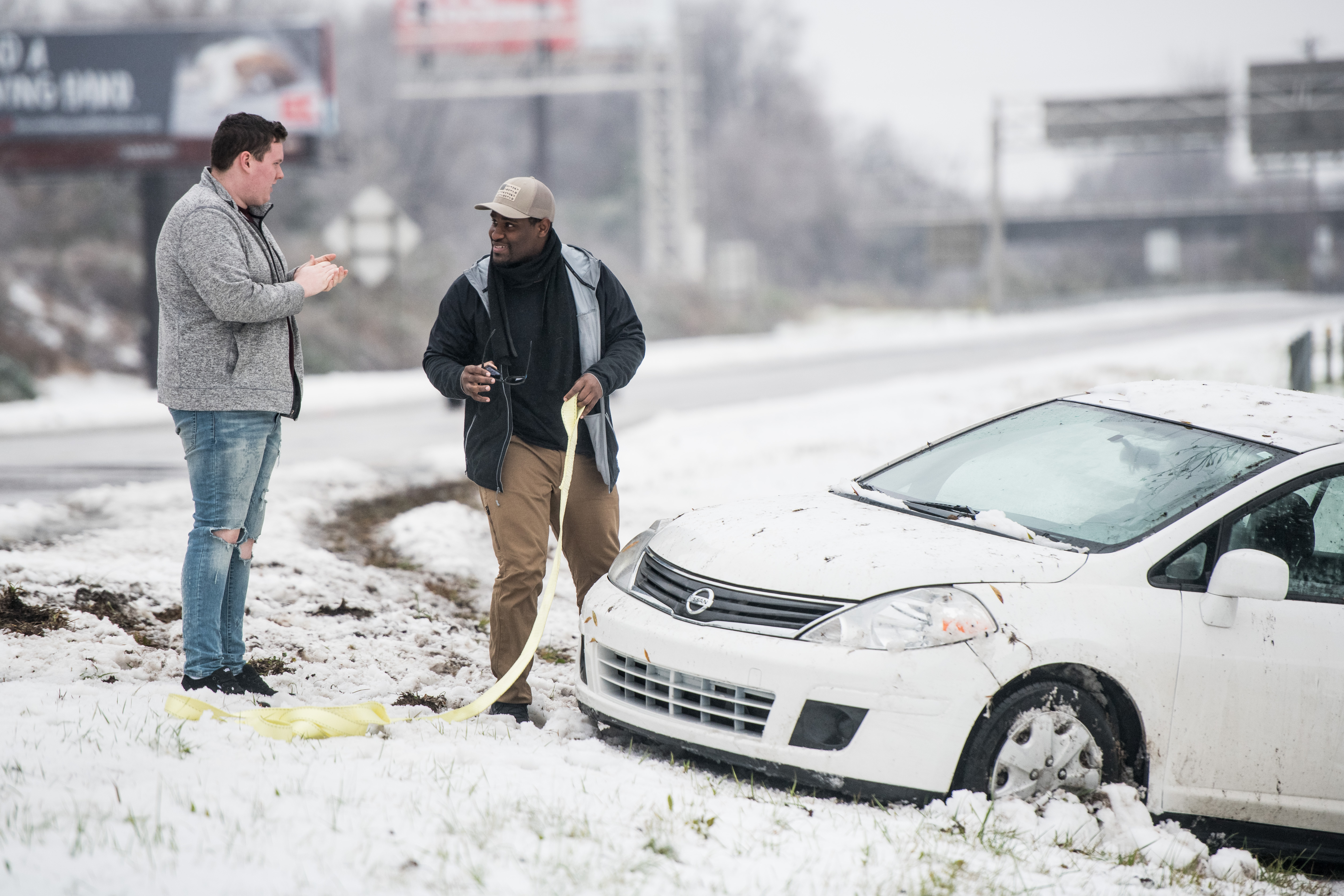 Two men prepare to pull a vehicle out of the snow after a motorist slid off the road on December 9, 2018 in Charlotte, North Carolina. Nearly 250,000 energy customers are without power because of the winter storm. (Photo by Sean Rayford/Getty Images)