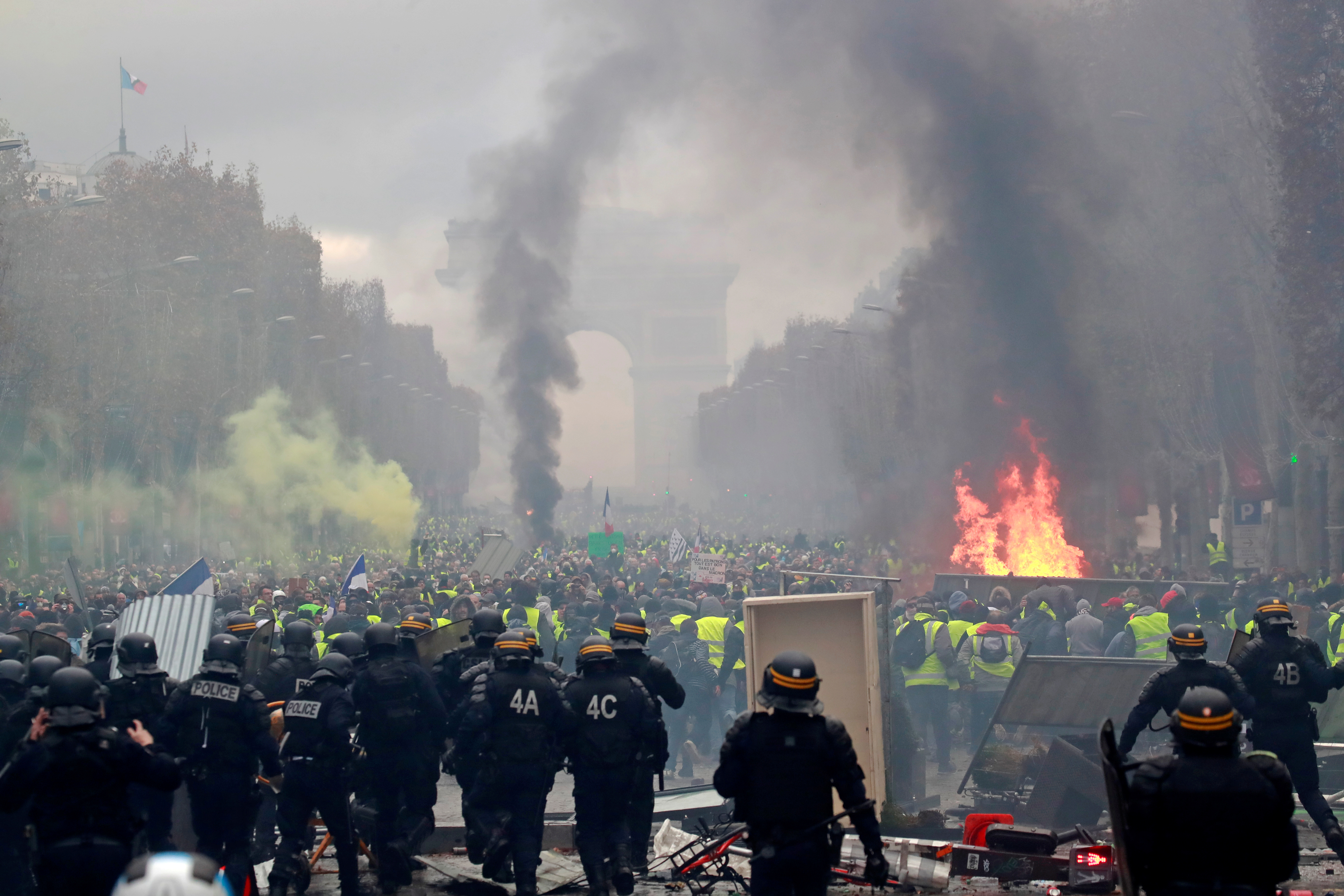 Protesters wearing yellow vests, a symbol of a French drivers' protest against higher fuel prices, run from police during riots on the Champs-Elysees in Paris, France, November 24, 2018. REUTERS/Gonzalo Fuentes