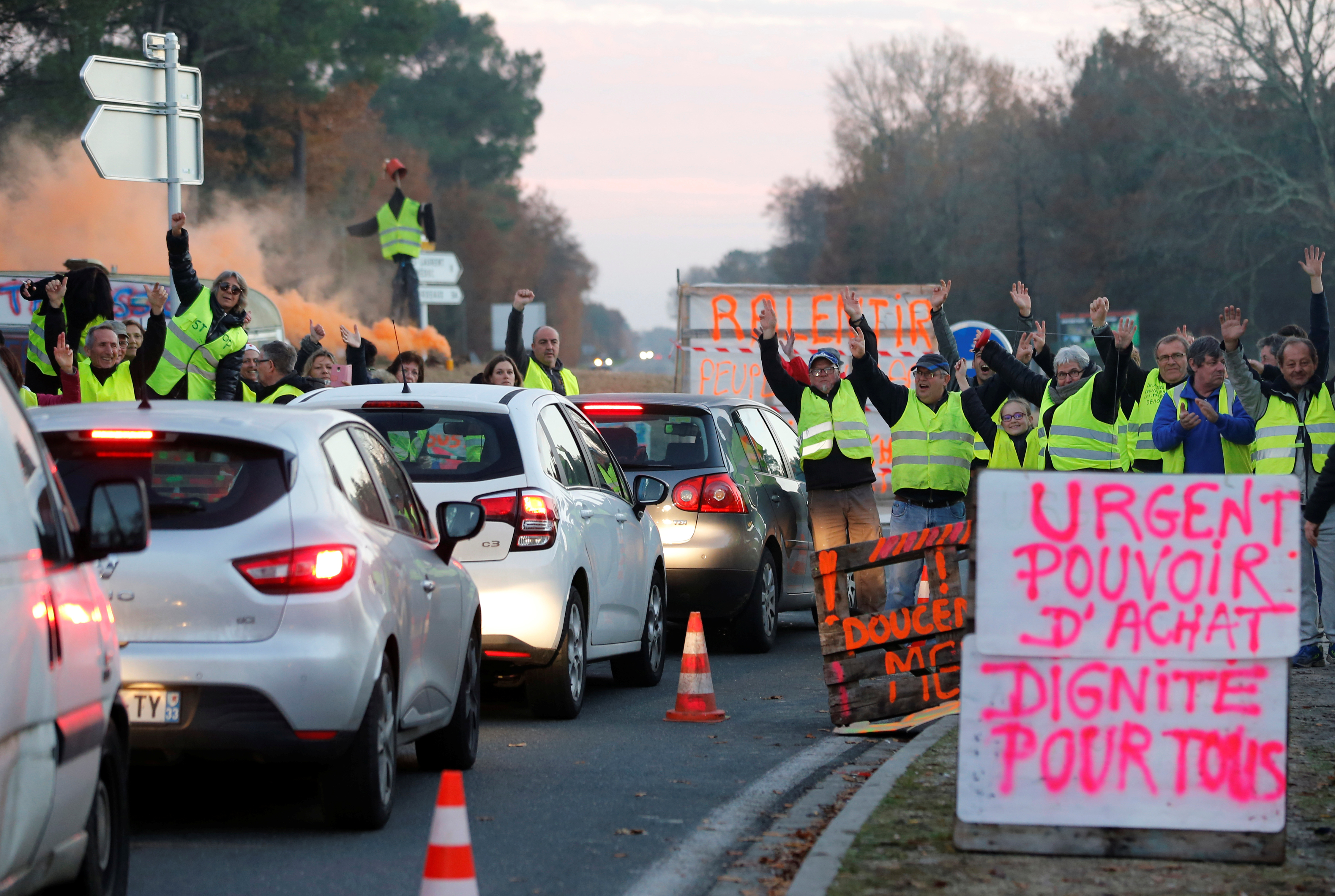 "Protesters wearing yellow vests, the symbol of a French drivers' protest against higher diesel fuel prices, occupy a roundabout in Cissac-Medoc, France, December 5, 2018. The slogan reads ""Urgent, purchase power, dignity for all"". REUTERS/Regis Duvignau"