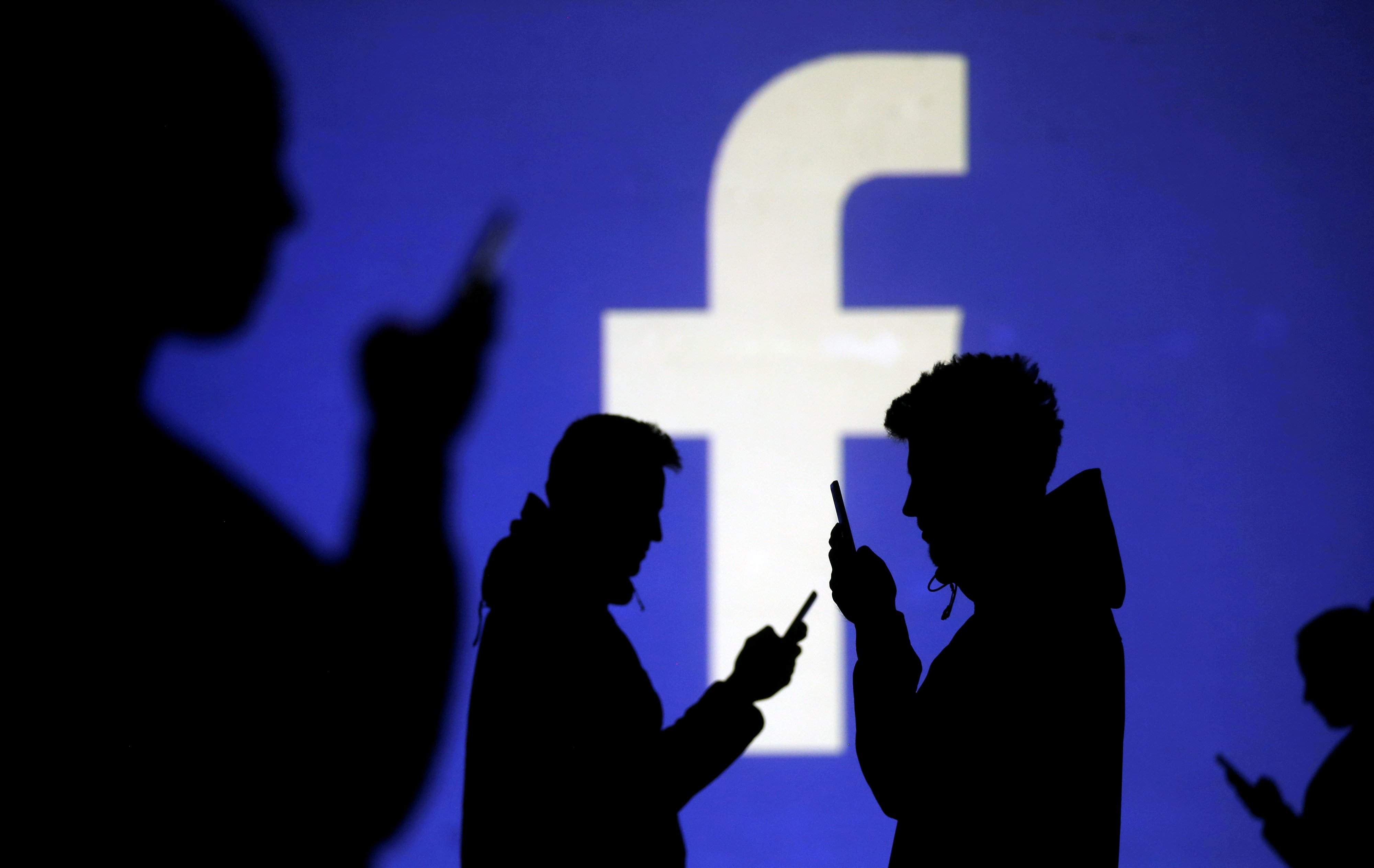 Silhouettes of mobile users are seen next to a screen projection of Facebook logo in this picture illustration taken March 28, 2018. REUTERS/Dado Ruvic/Illustration/File Photo - RC1D880ABF30