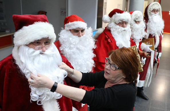 """Christina Brunkhorst (R), employee of the job centre in Rostock, northeastern Germany, inspects candidates in Santa Claus """"uniforms"""" applying for a job at the centre's Santa Claus agency on December 11, 2018. (Photo by Bernd WUESTNECK / dpa / AFP)"""